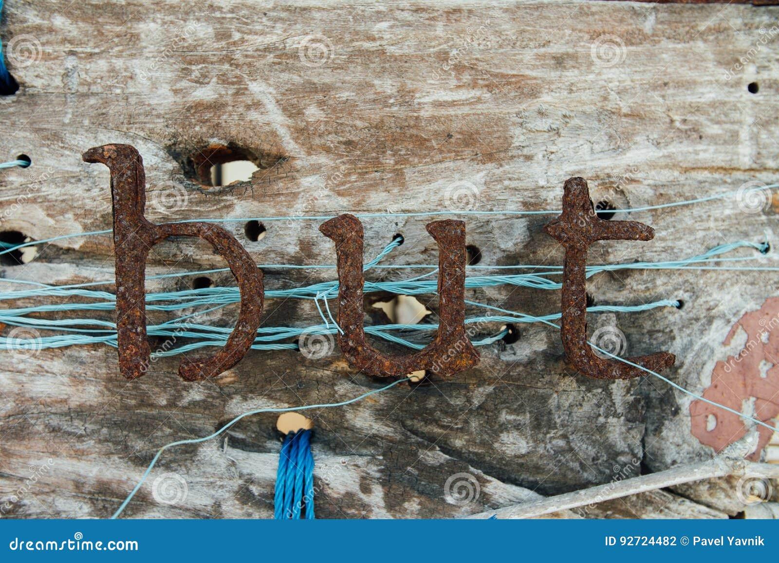 老铁信件 与文本的葡萄酒牌从铁腐蚀在标志上写字