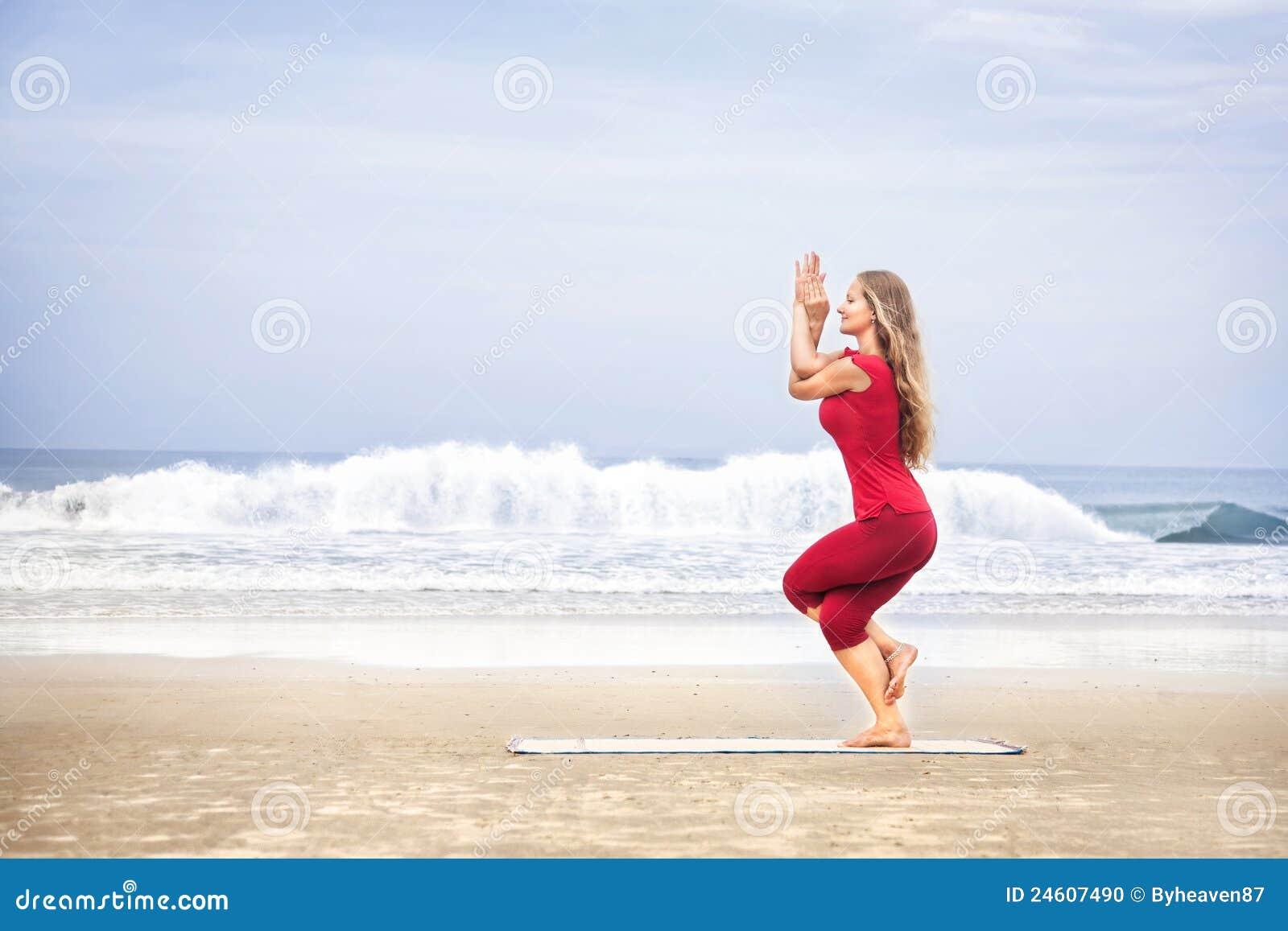 背景海灘布料老鷹garudasana頭發長的海洋姿勢紅色女子瑜伽年輕人.圖片