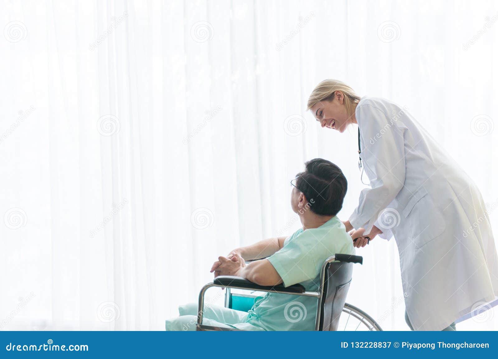 耐心年长人在有生理治疗师身分的一个轮椅坐在愉快和微笑后