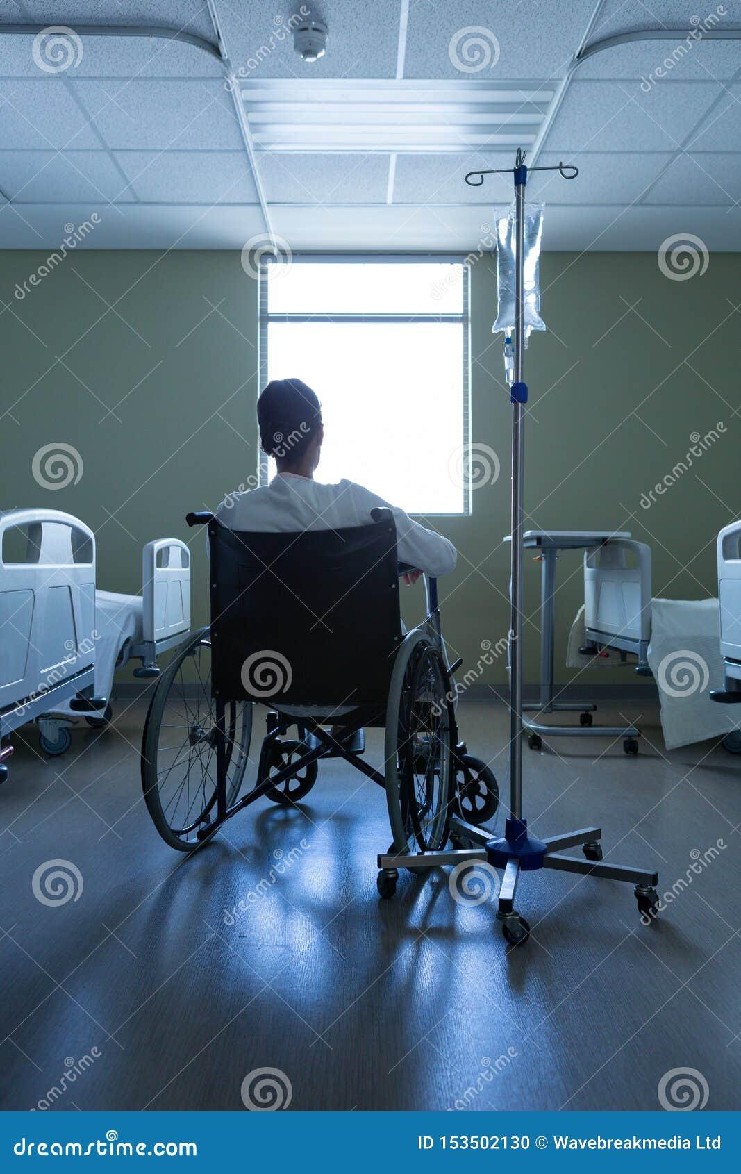 耐心看通过窗口,当坐在轮椅在医院时