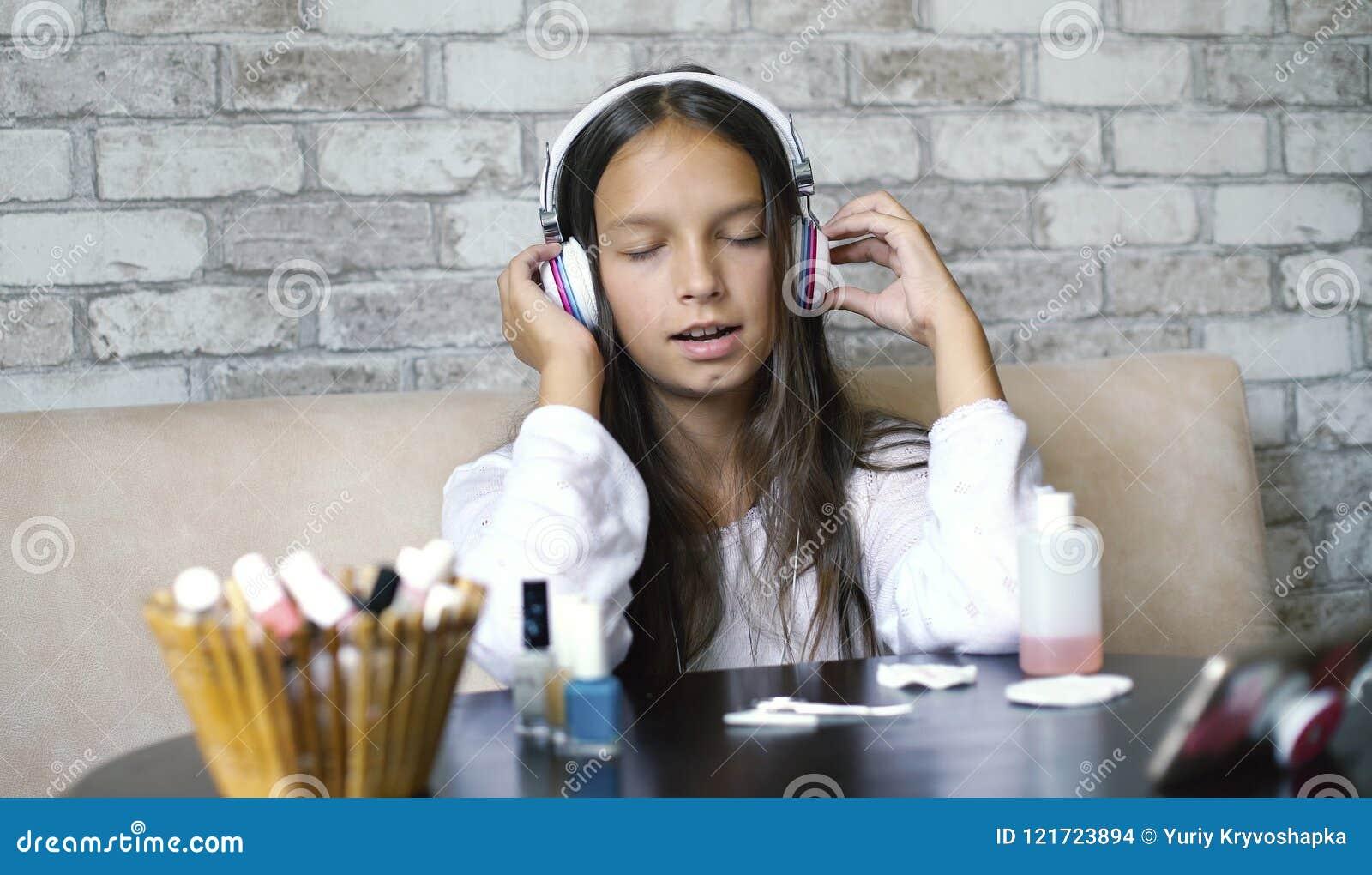 耳机和家庭衣裳听的音乐的逗人喜爱的女孩在电话和唱歌,当做修指甲时