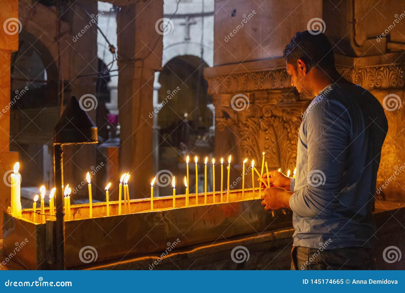 耶路撒冷,以色列,09/11/2016:一个相信的人在圣洁坟墓的寺庙投入蜡烛并且祈祷
