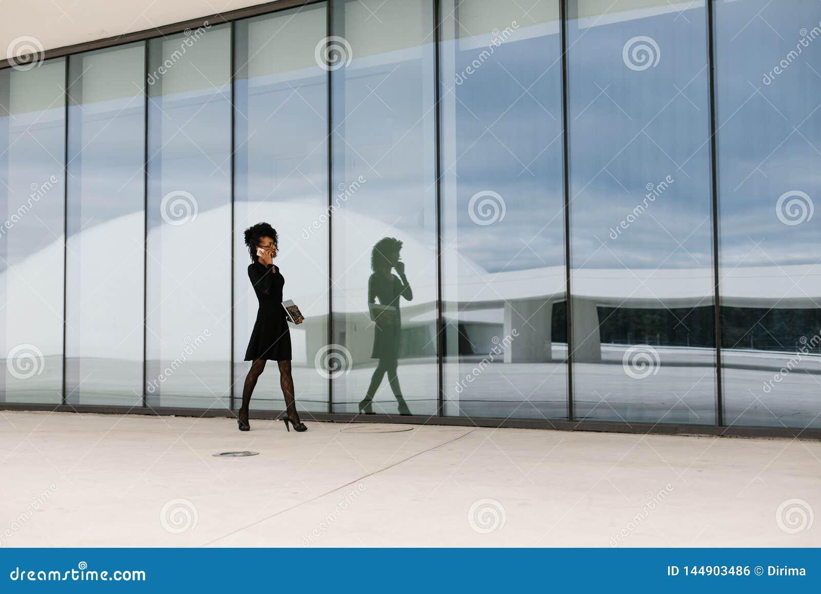 职业妇女走和谈话在手机外面
