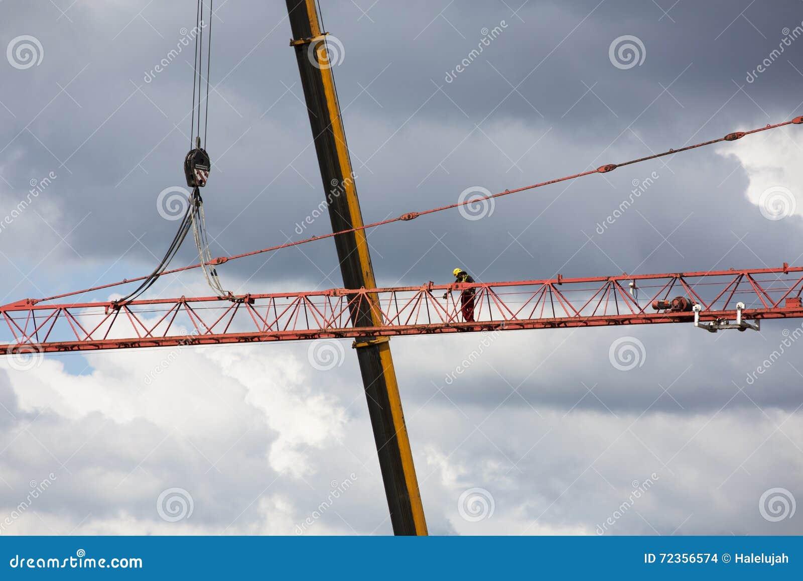 聚集在剧烈的多云背景的起重机 高度塔吊