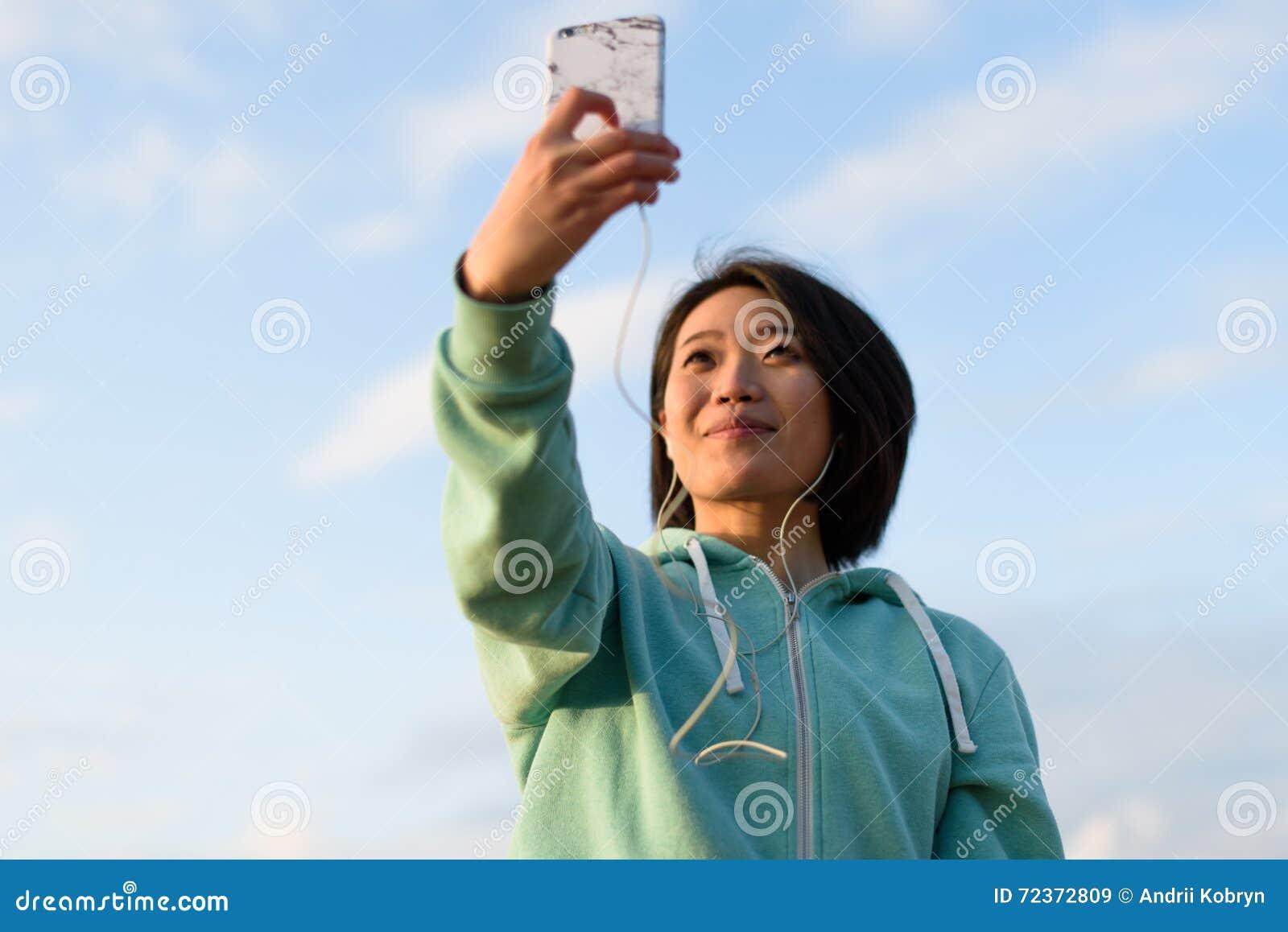 肉欲的日本妇女画象有采取selfie的短发的室外使用她的电话 蓝色多云天空背景