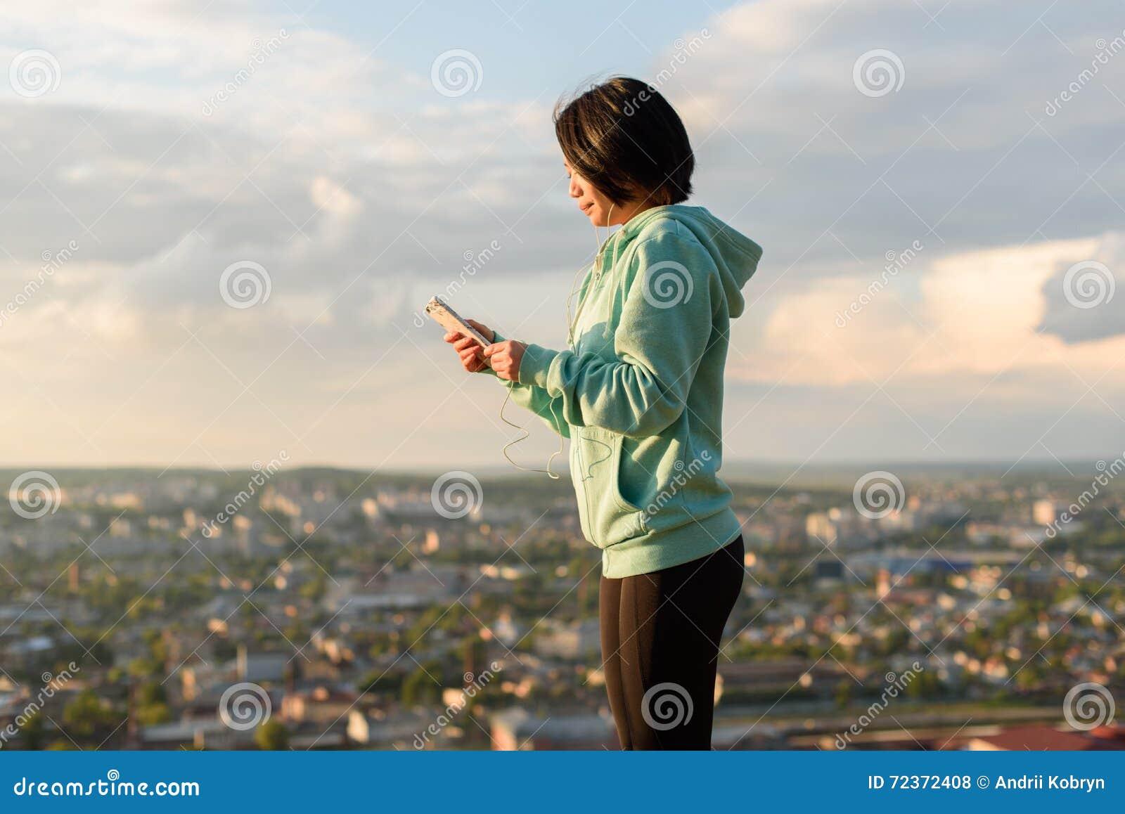 肉欲的年轻亚裔妇女听到在耳机的音乐 被弄脏的城市背景 早晨锻炼概念