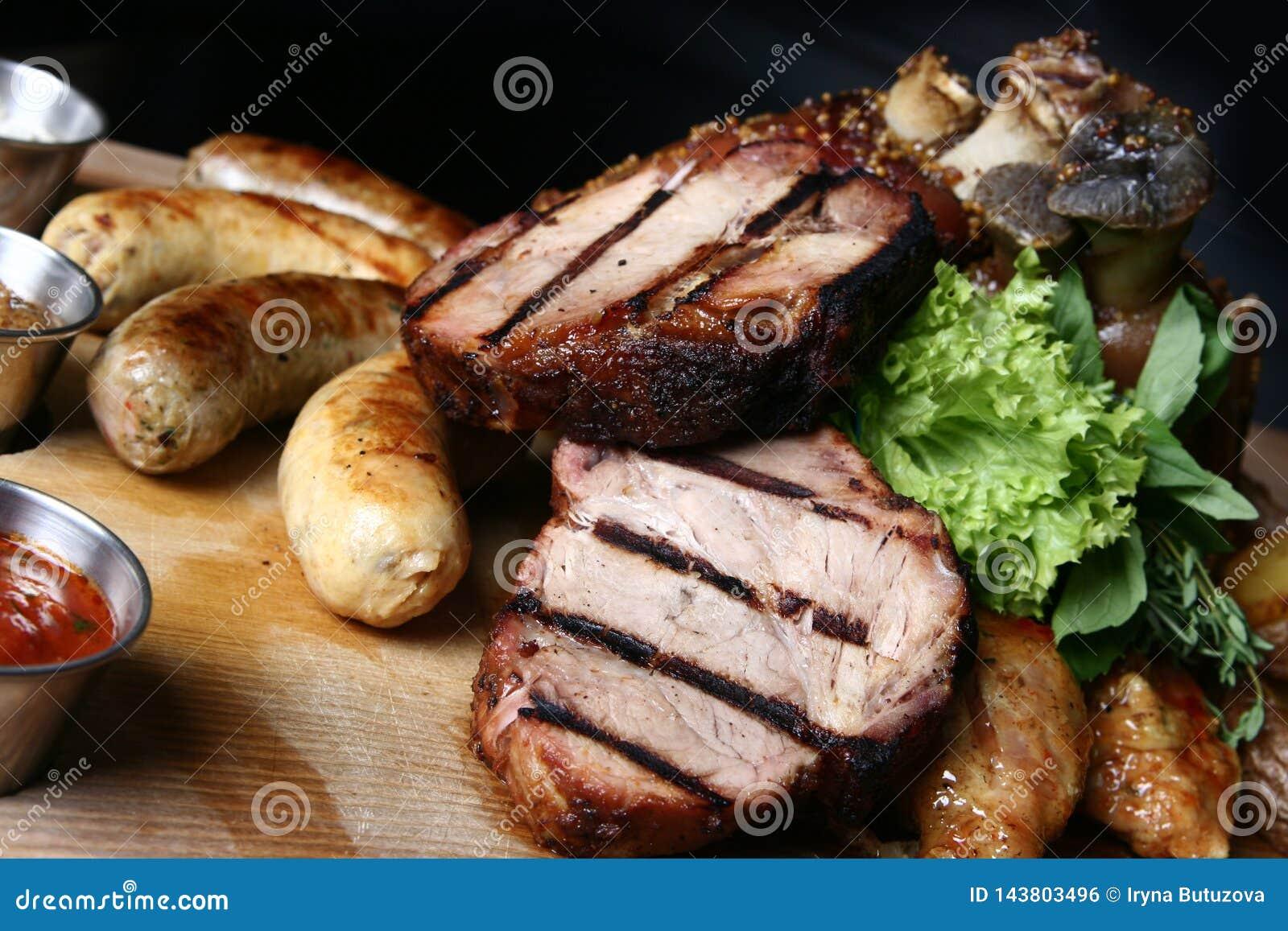 肉盘用牛排、猪肉指关节、自创香肠和被烘烤的土豆