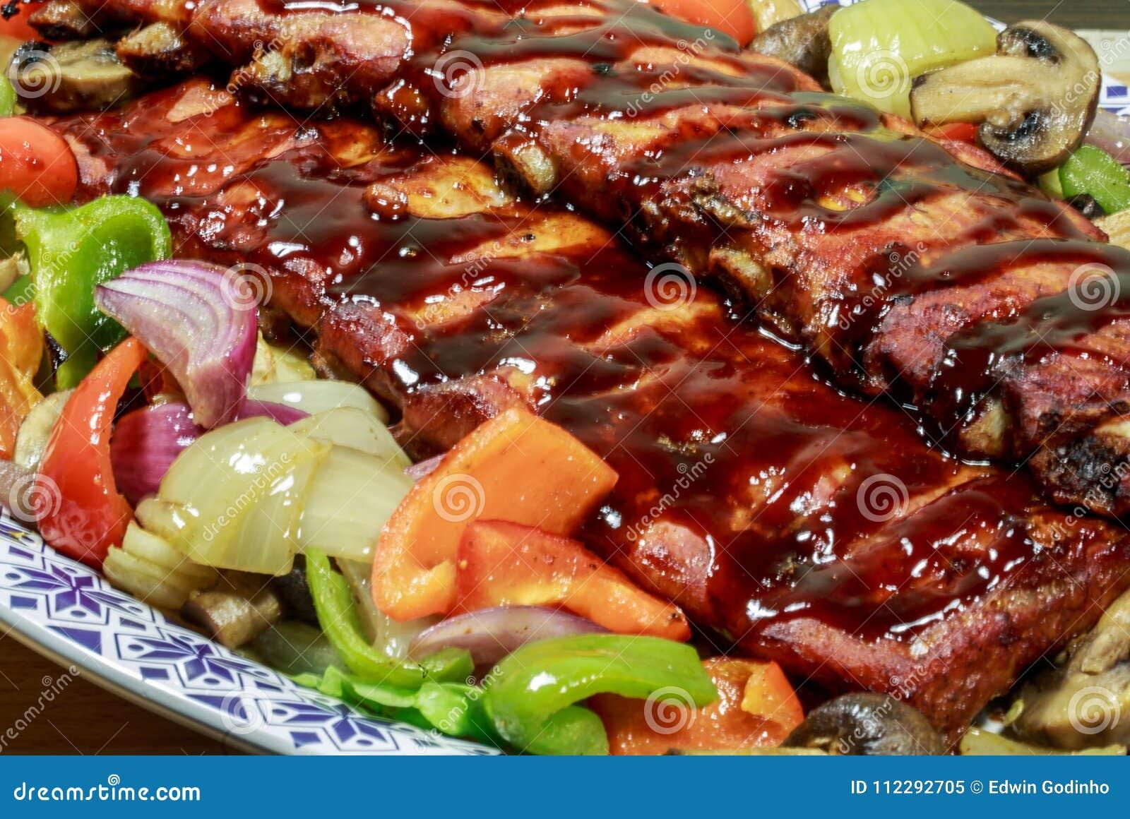 肋骨机架烹调了与烤肉汁和烘烤菜