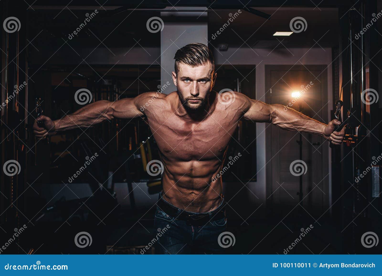 肌肉做在健身房的爱好健美者英俊的人锻炼与赤裸躯干 有腹肌和二头肌的坚强的运动人