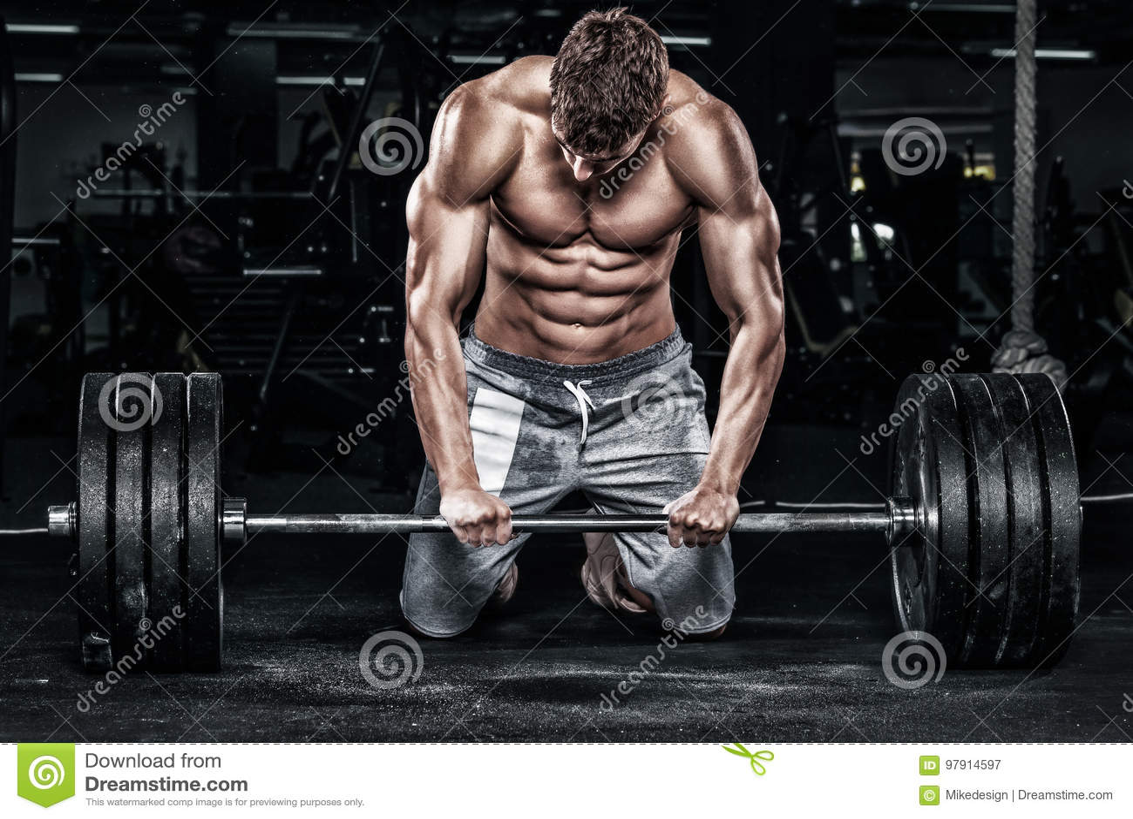 肌肉年轻健身炫耀与杠铃的人锻炼在健身健身房