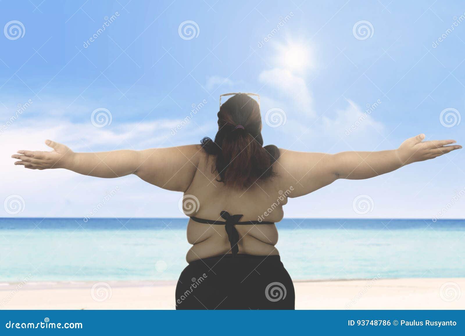 肥胖在海滩的妇女佩带的游泳衣