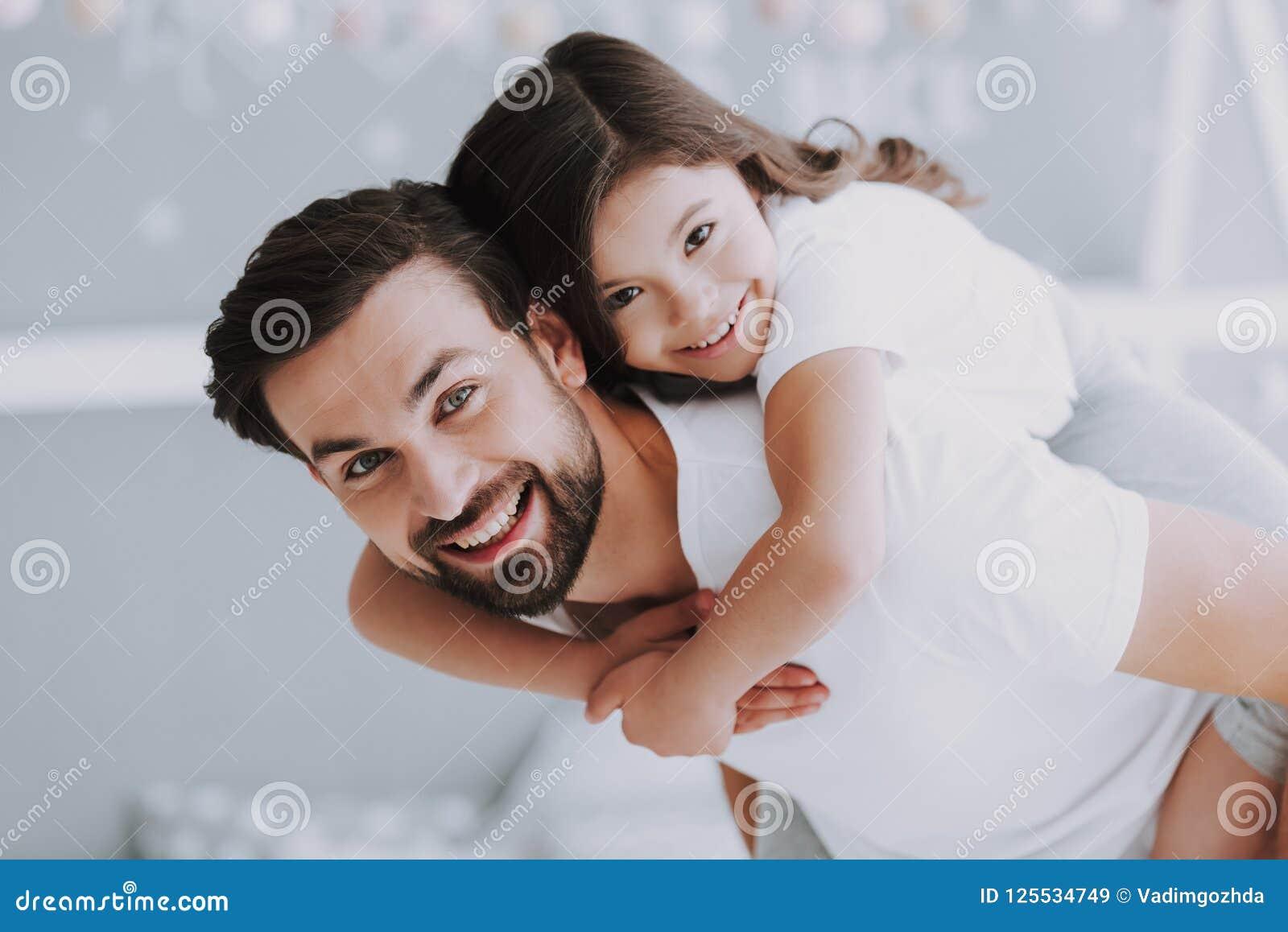 肩扛乘驾的逗人喜爱的年轻女儿与爸爸