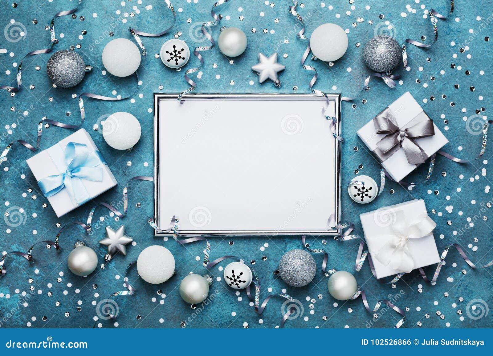 背景圣诞节魔术 与xmas装饰、礼物盒、五彩纸屑和银衣服饰物之小金属片的框架在葡萄酒蓝色台式视图