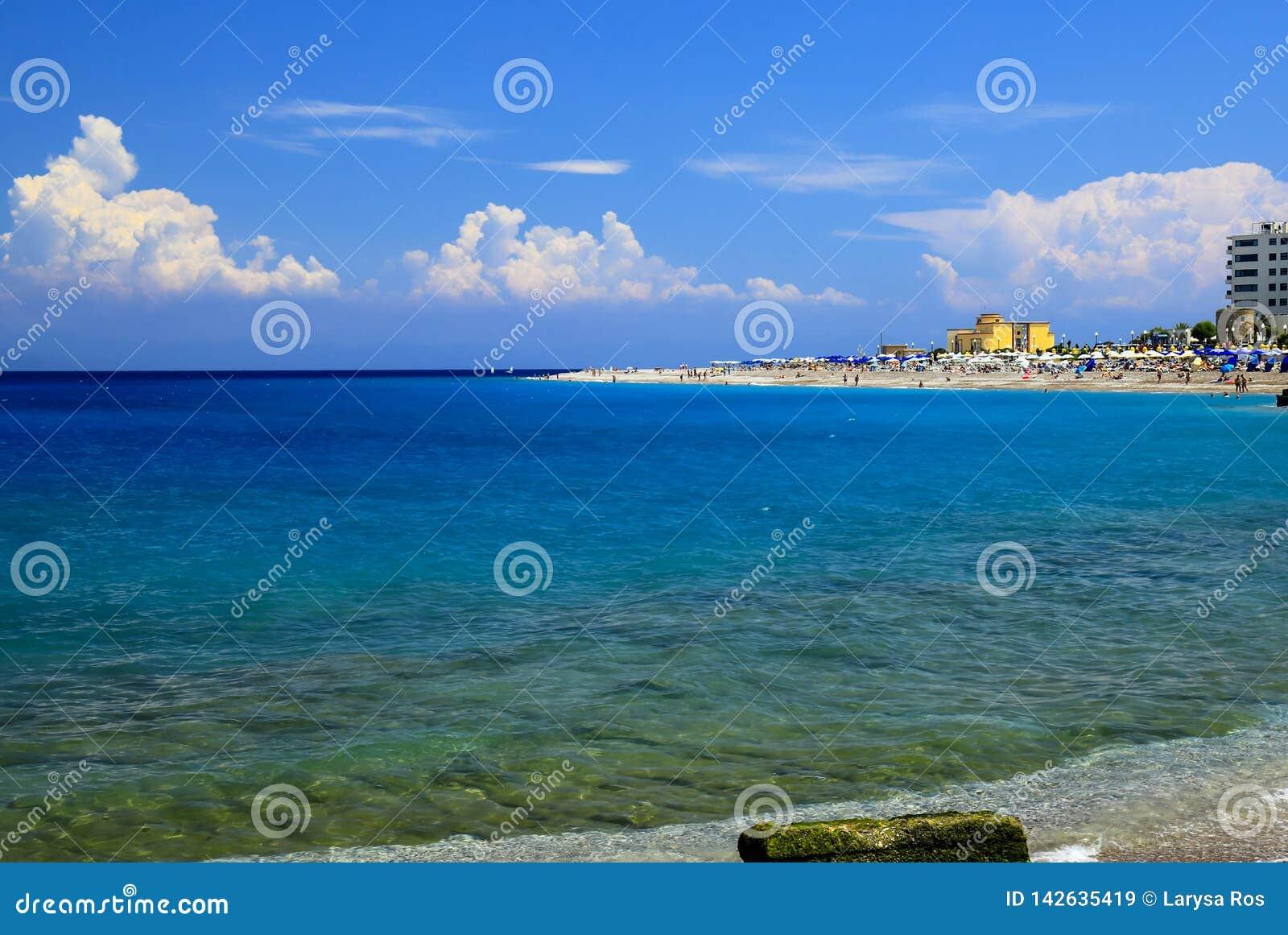 背景峡湾光芒海运星期日 美丽如画的夏天海滩,在海浪线的小卵石在美丽的绿松石海,罗得岛,Greee