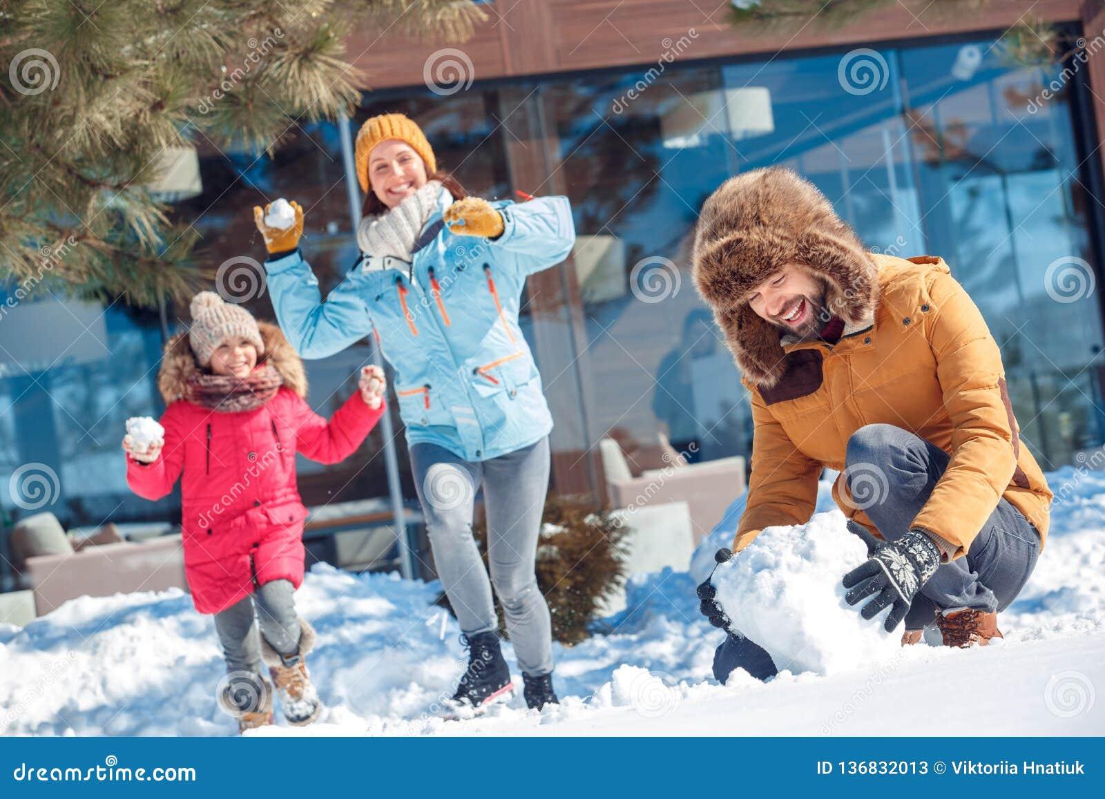 背景海滩异乎寻常的做的海洋沙子雪人热带假期白色冬天 户外一起家庭做战斗的时间人雪球,当跑向命中时的妇女和女孩
