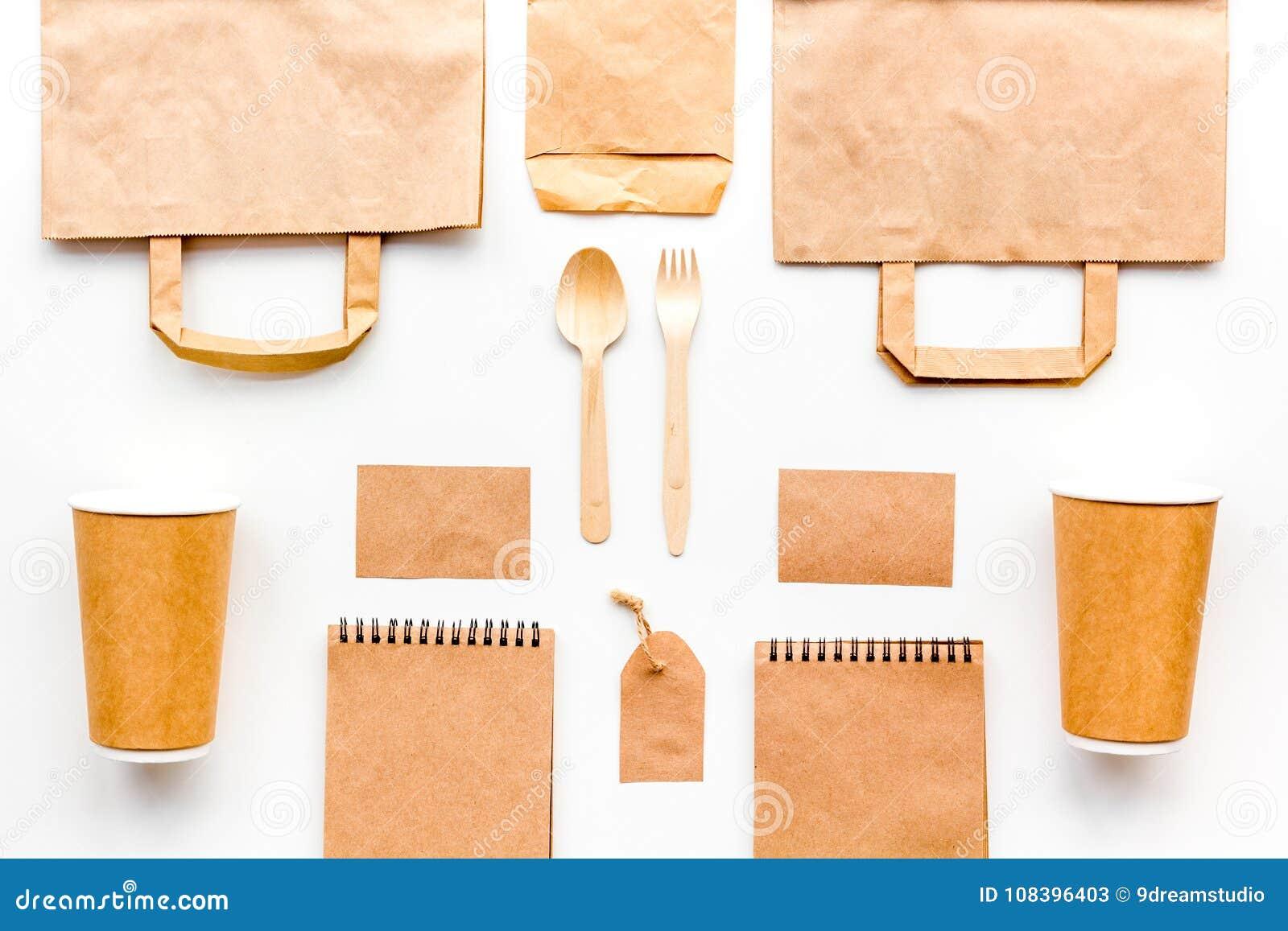 背景色的一次性叉子玻璃塑料集合碗筷透明白色 纸杯,匙子,在包装纸样式白色的袋子、标签和笔记本顶视图嘲笑附近分叉