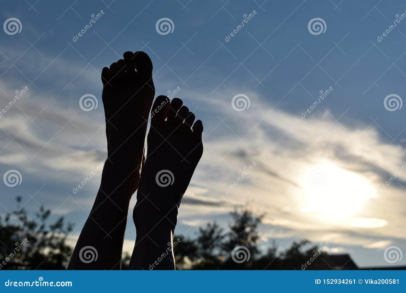 腿黑暗的剪影在日落的在天空 腿的脚被举对太阳