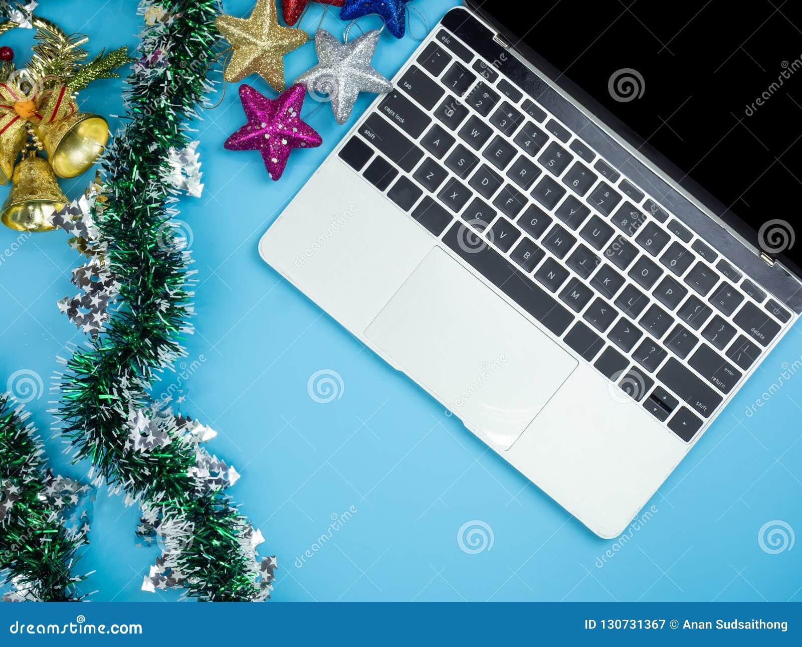 膝上型计算机和装饰顶视图在蓝色被隔绝的背景 圣诞节和新年假日概念