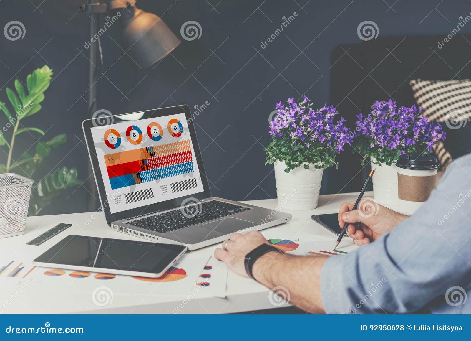 膝上型计算机特写镜头有图表、图和图的在屏幕上 在桌上是数字式片剂,纸图表,房子植物