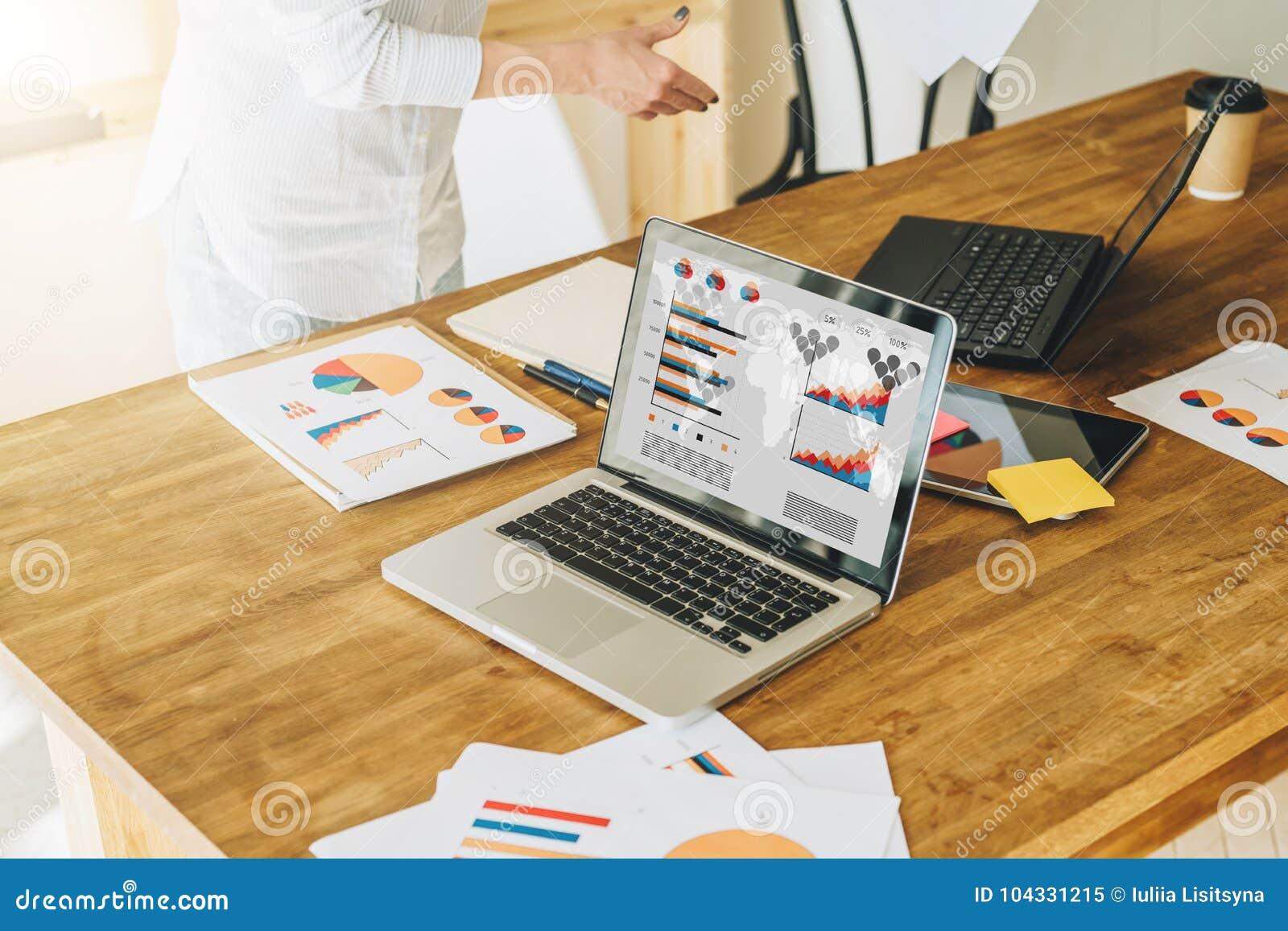 膝上型计算机特写镜头有图表的,图,在屏幕上的图在木桌上 附近纸图表,数字式片剂
