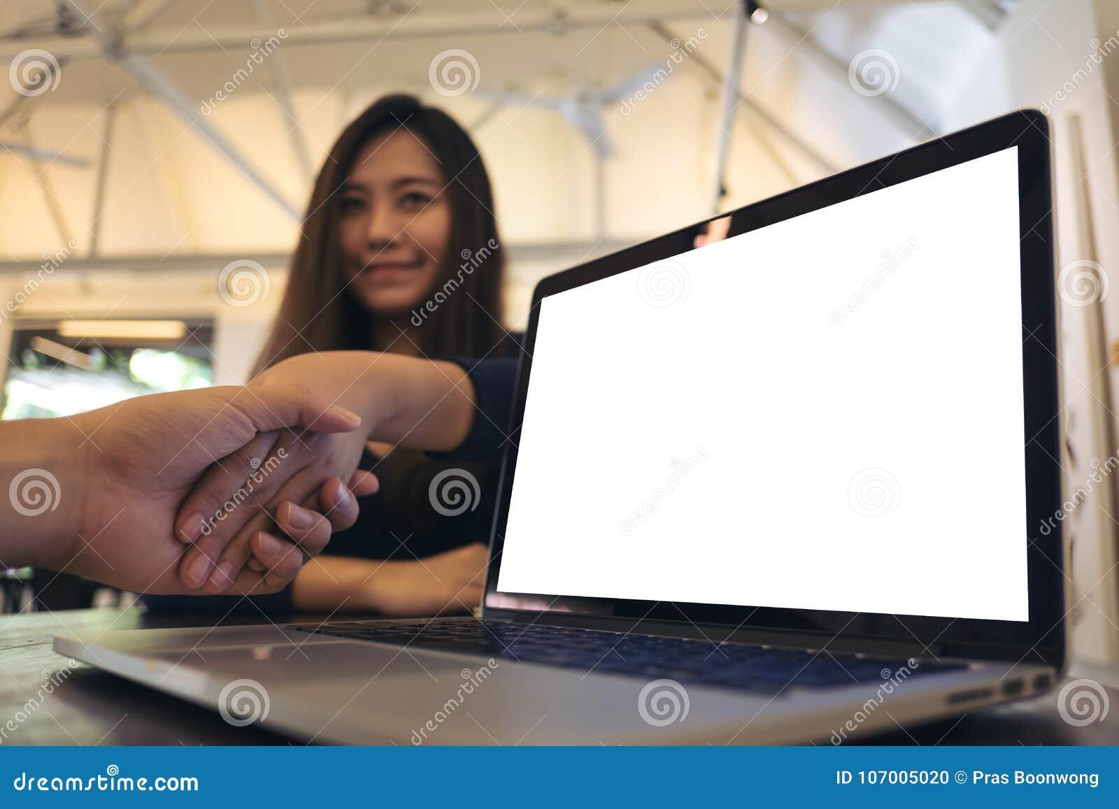 膝上型计算机的大模型图象有空白的白色屏幕的在与商人的木震动的桌和女实业家上手