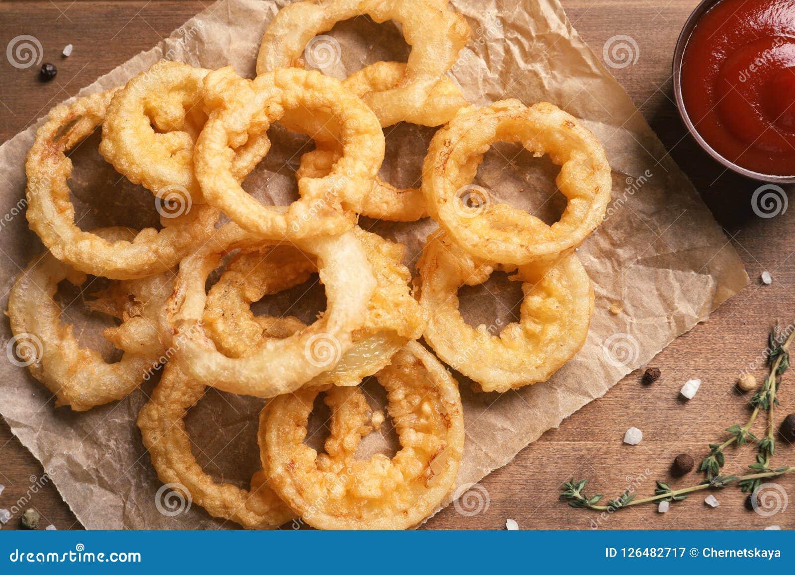 自创嘎吱咬嚼的油煎的洋葱圈和调味汁在木背景