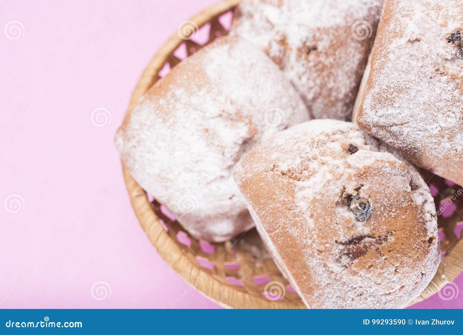 自创松饼用葡萄干和搽粉的糖在一个柳条筐在浅粉红色的背景