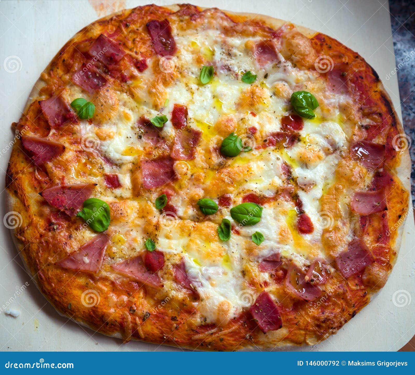 自创比萨用蕃茄、无盐干酪和蓬蒿 在黑暗的石桌上的顶视图