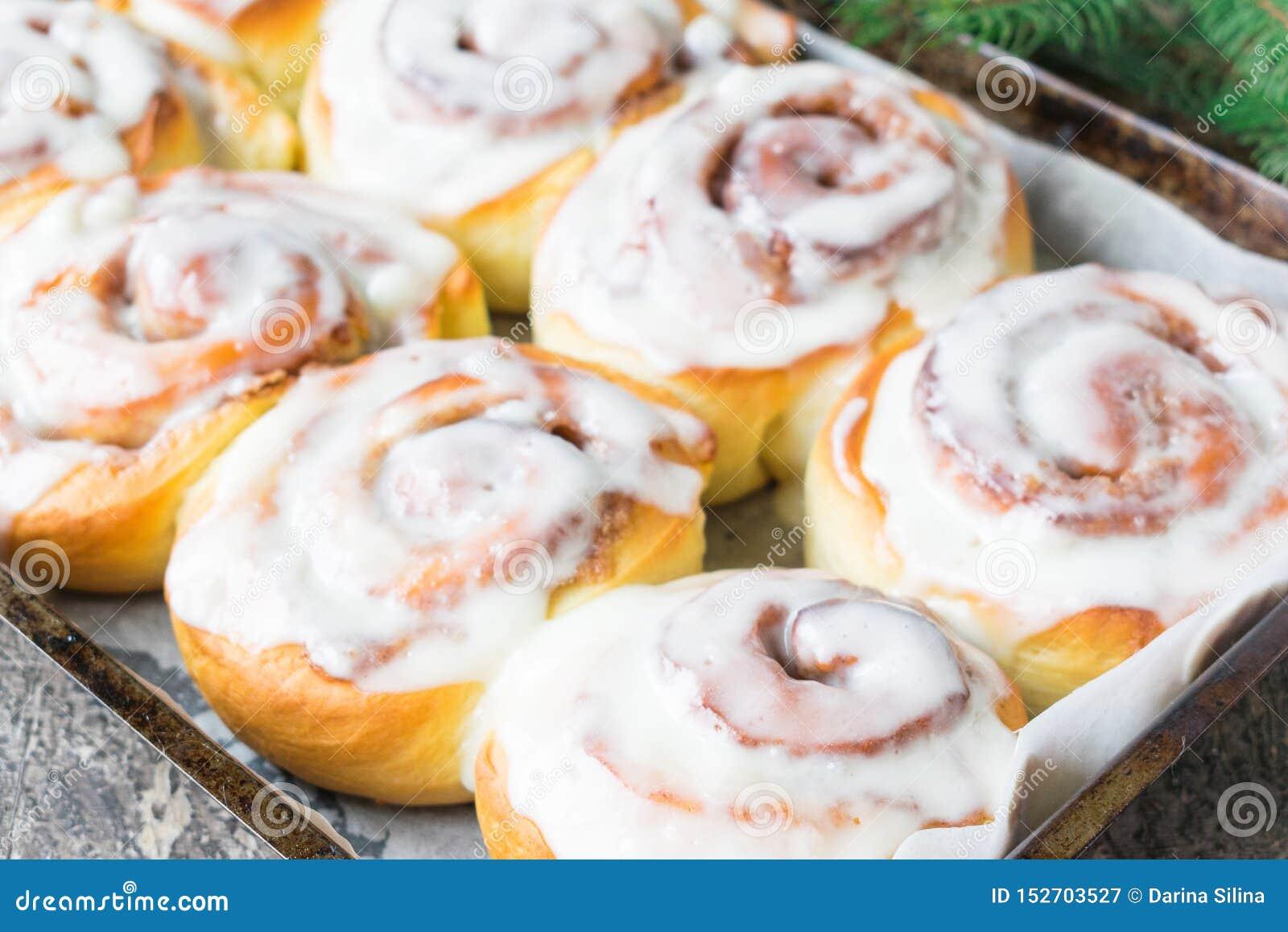 自创Cinnabon小圆面包用桂香和奶油在白色板材在木桌和餐巾上 m r