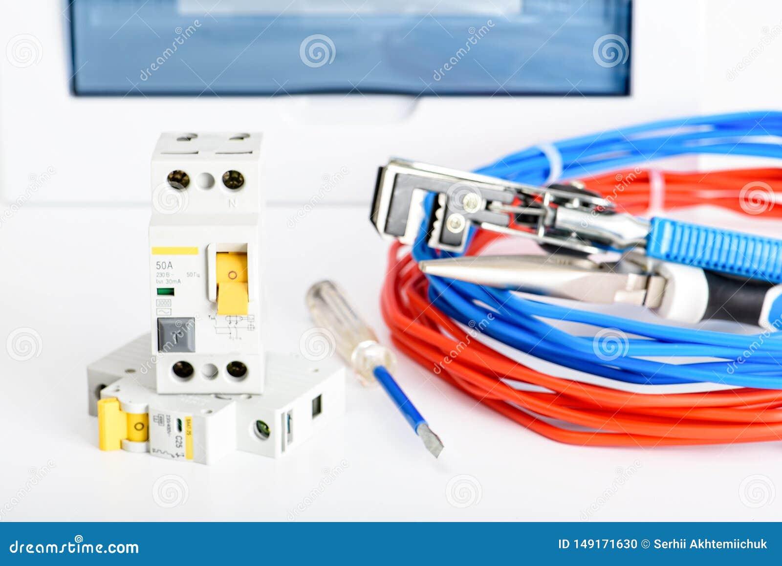 自动开关、配电盒、缆绳和数字式多用电表在白色背景 电机设备