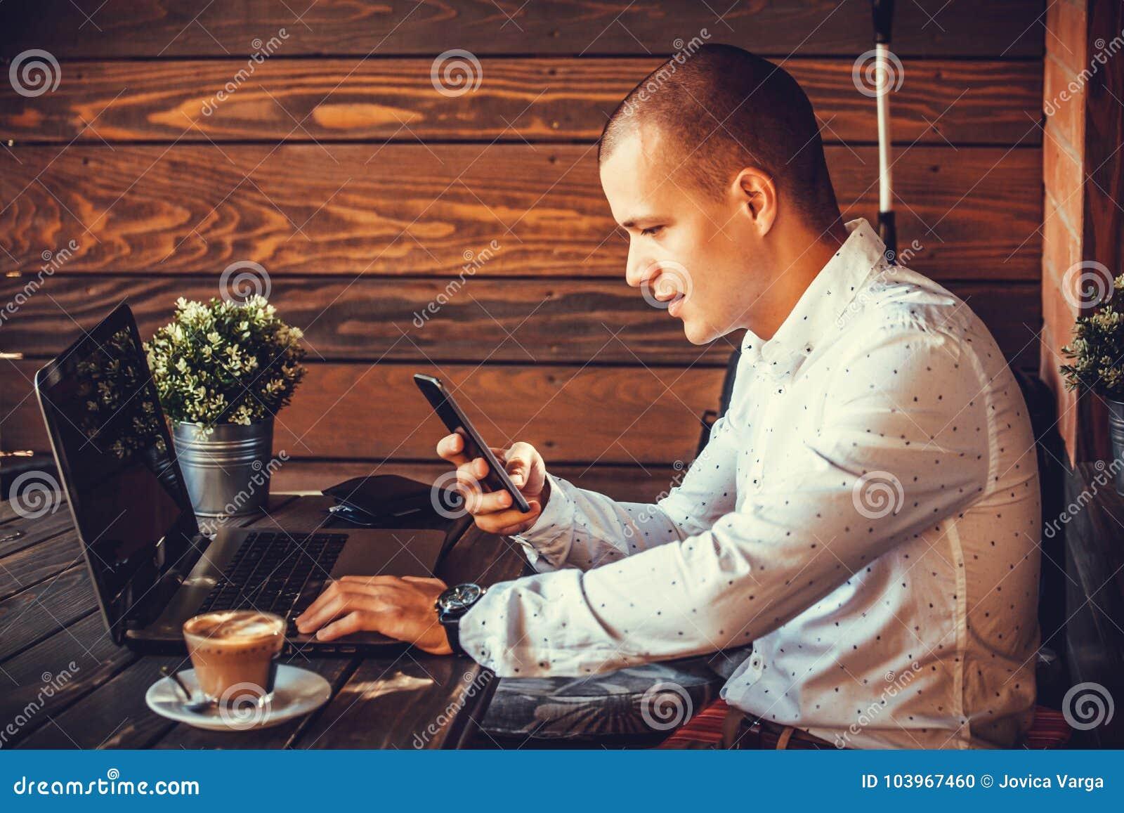 自己经营的愉快的人与膝上型计算机和一个巧妙的电话一起使用