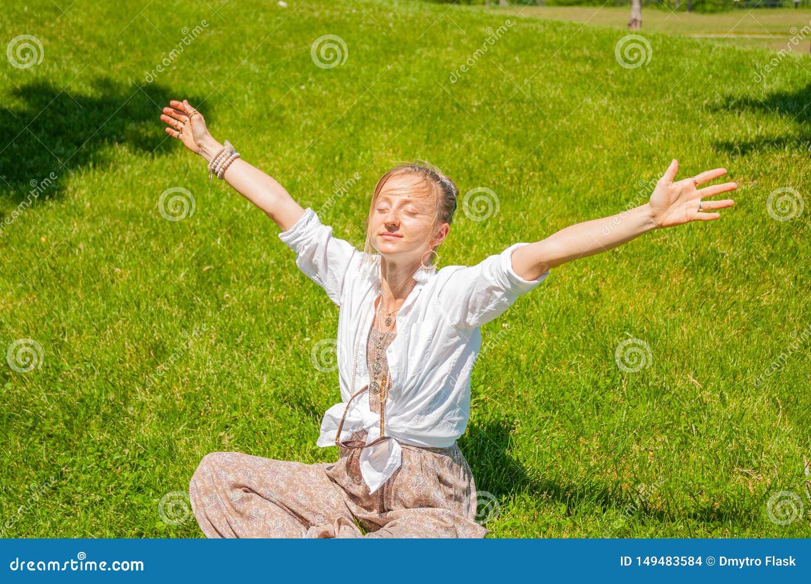 自由和愉快的片刻 有举的她的手美女坐草,享受好日子