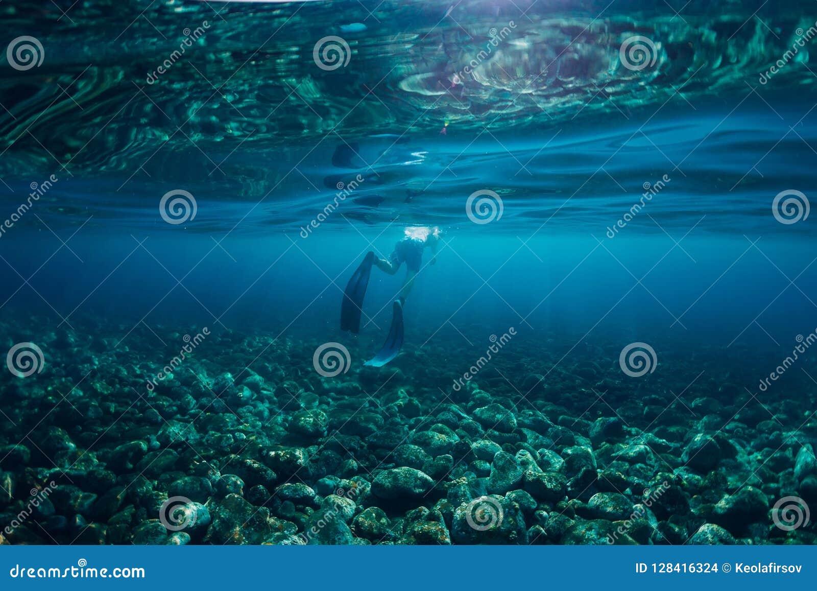 自由潜水者游泳在海洋,与阳光的水下的照片