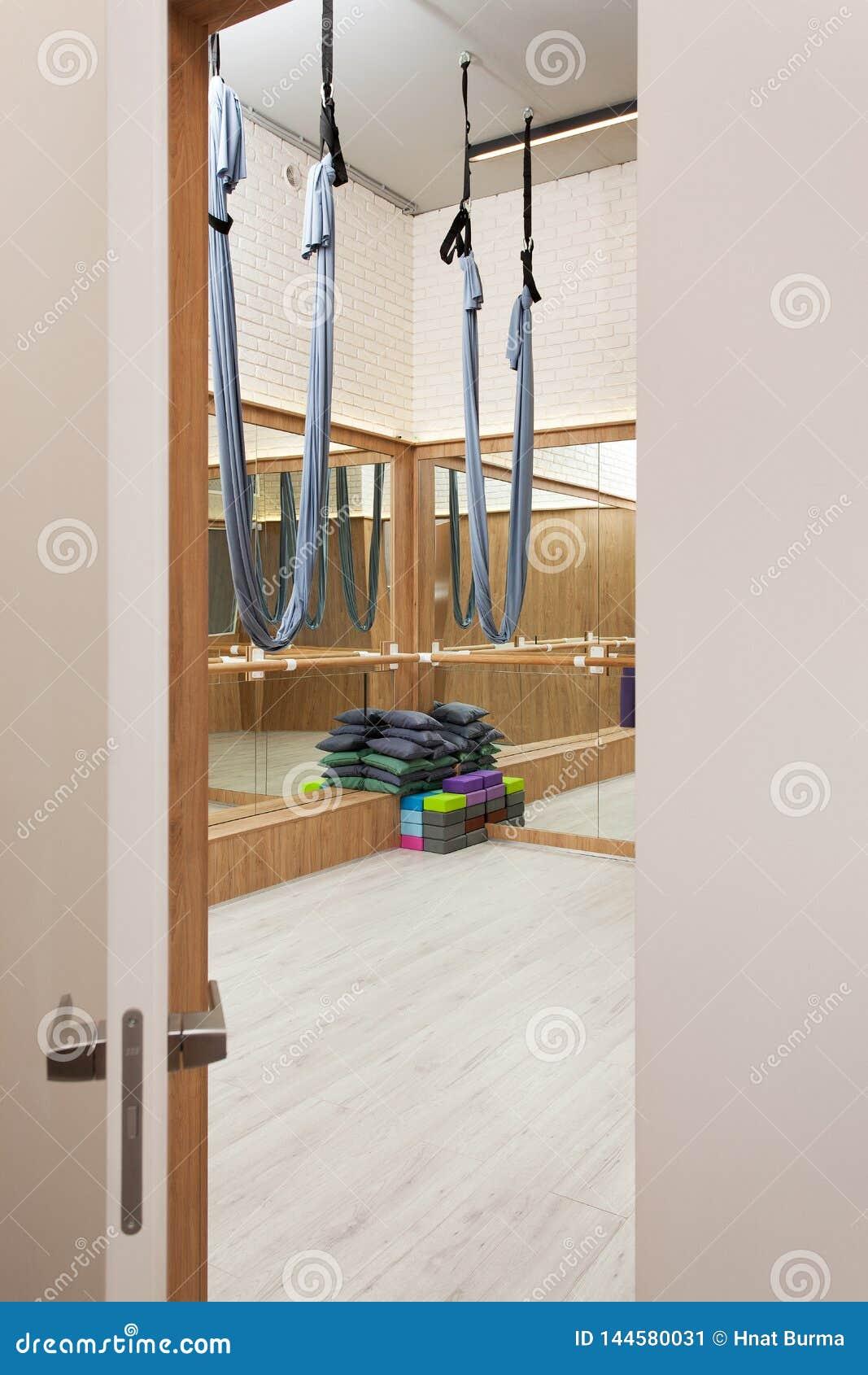 舒展与空中瑜伽丝绸吊床和镜子的演播室内部