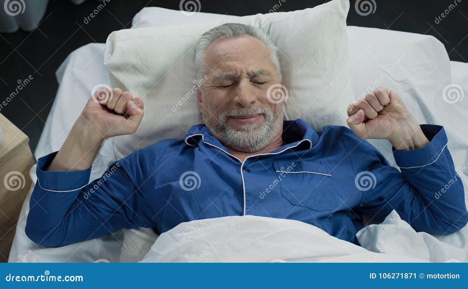 舒展在他的床上的领抚恤金者在唤醒以后早晨,健康睡眠