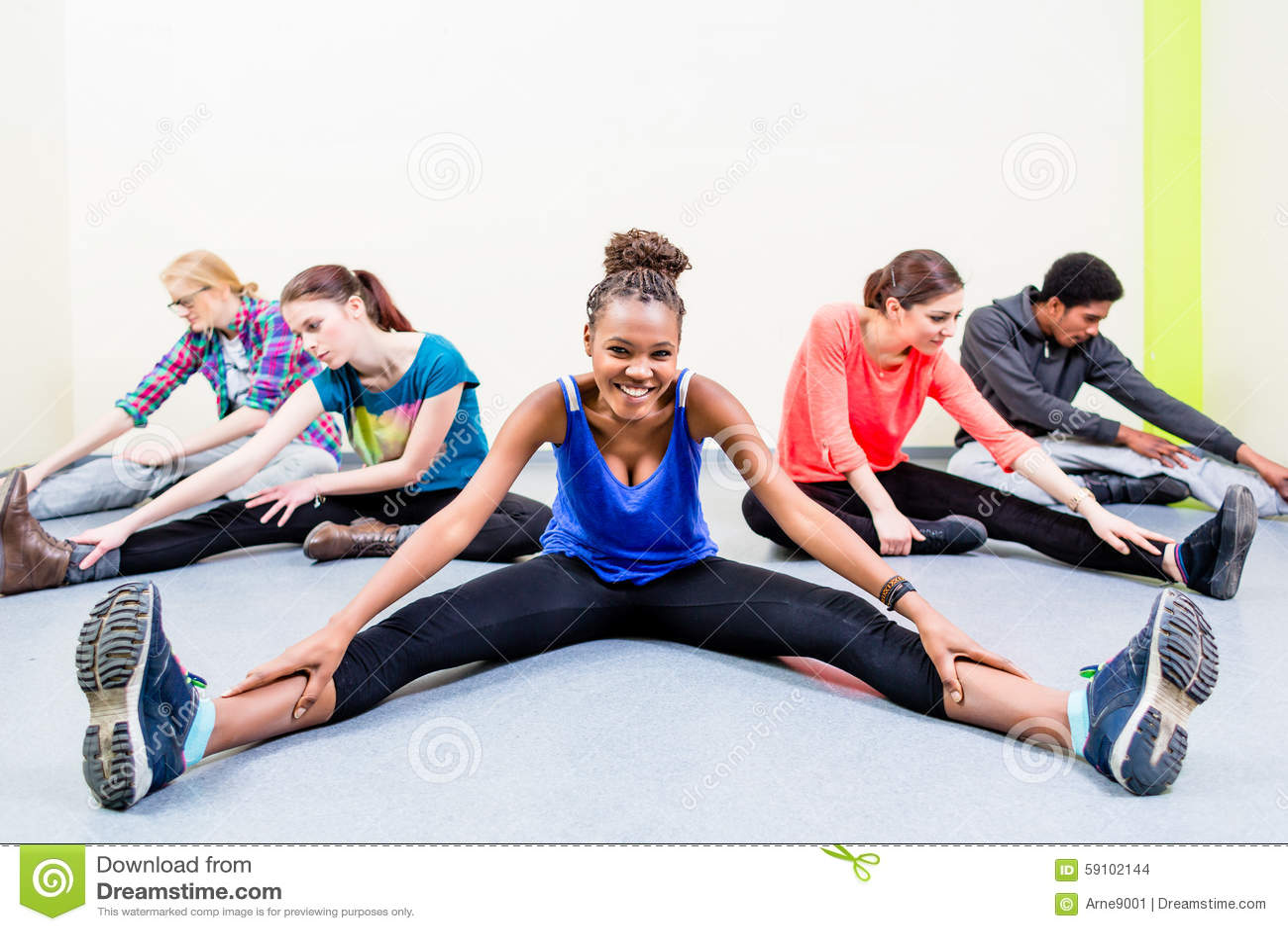 舒展在体操健身房的人们腿