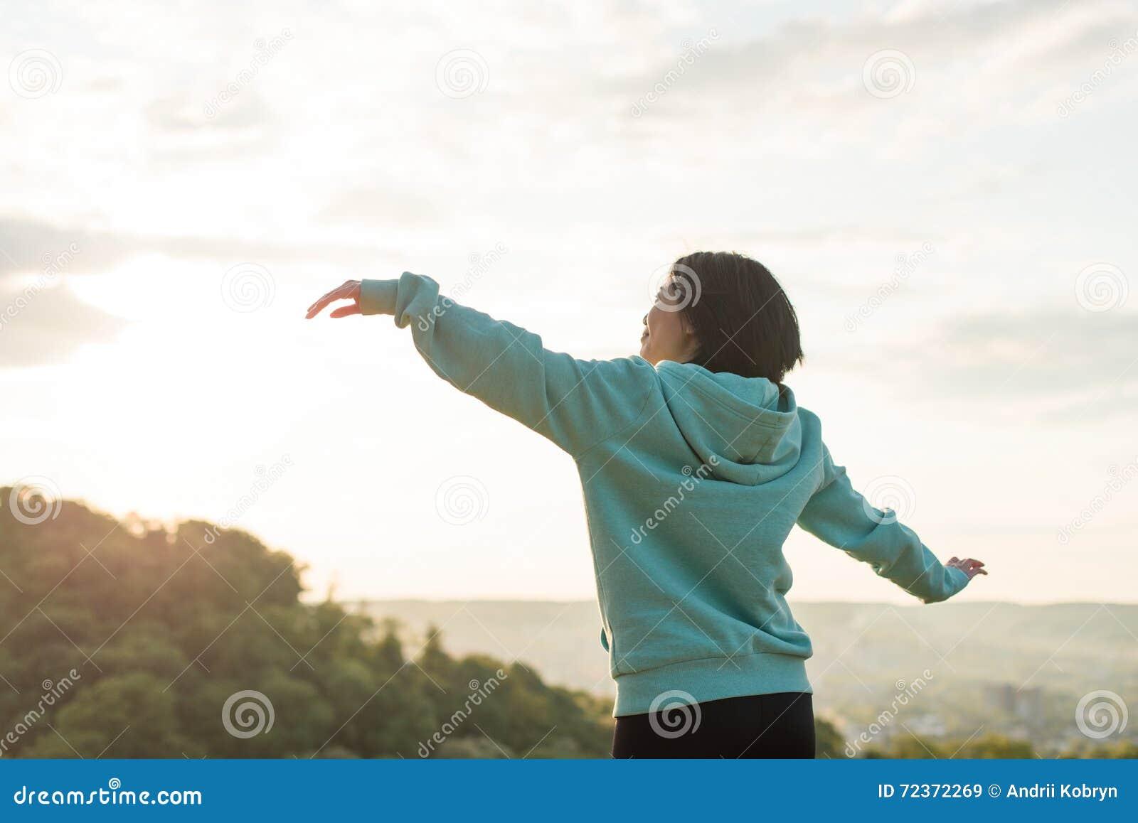 舒展在蓝天背景的美丽的亚裔妇女 放松的片刻