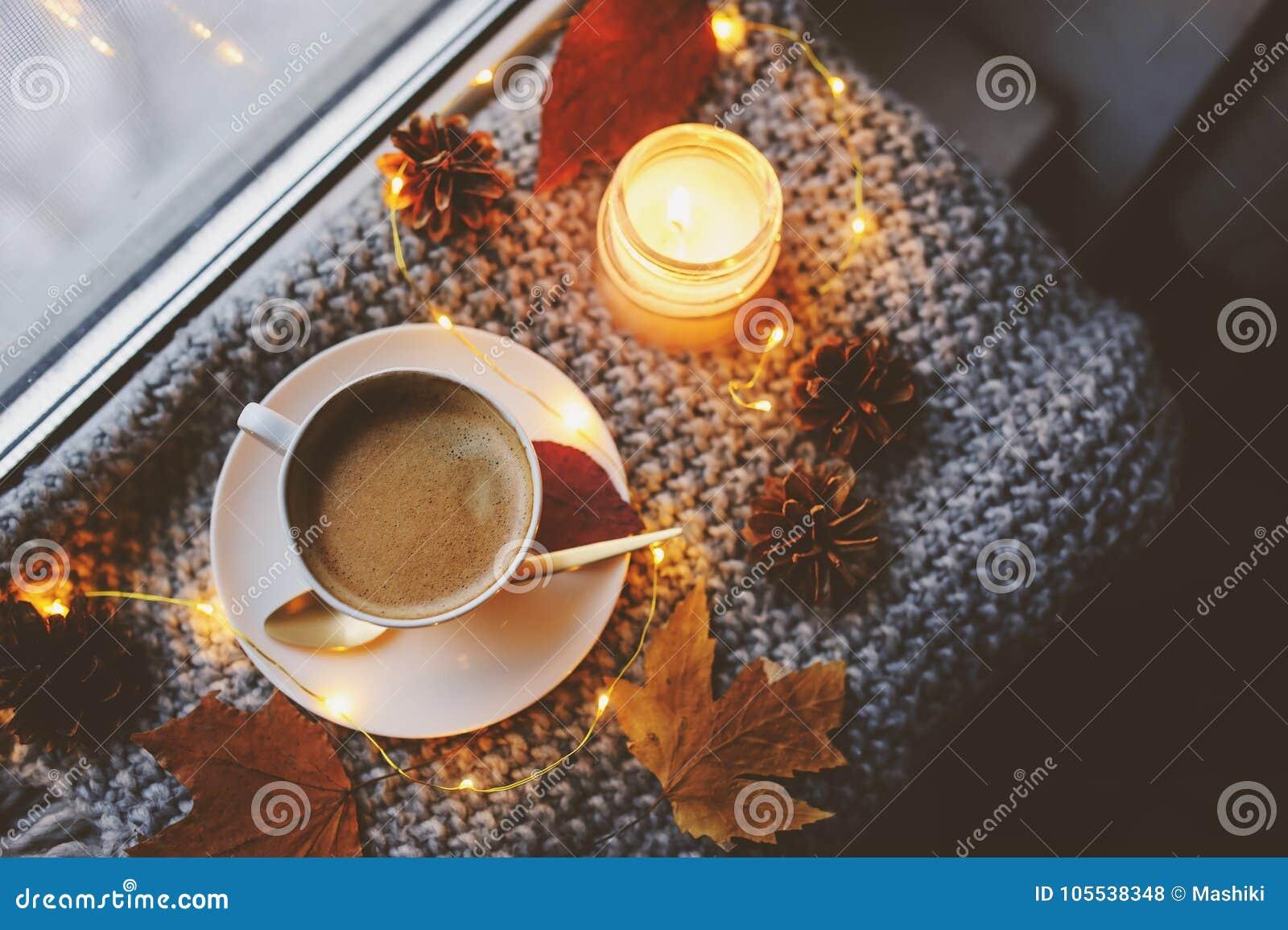 舒适冬天或秋天早晨在家 与金金属匙子,温暖的毯子、诗歌选和蜡烛光的热的咖啡