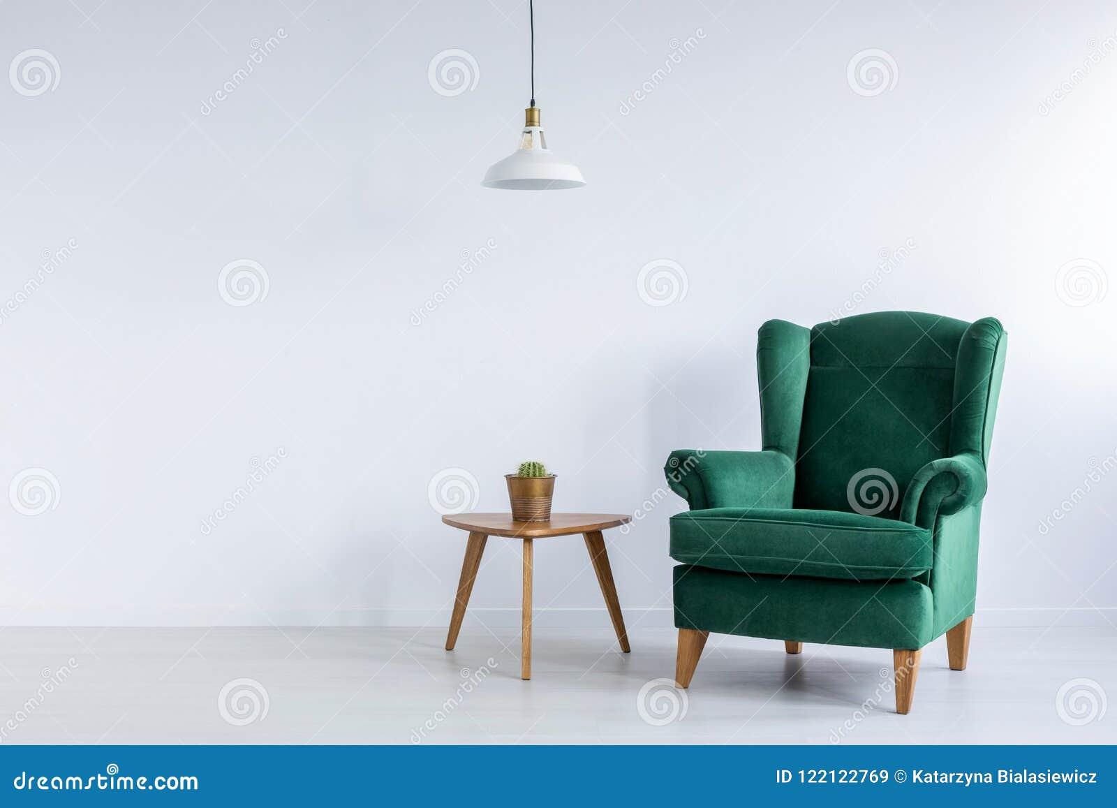 舒适,鲜绿色、翼扶手椅子和一个仙人掌在一张木桌上在白色客厅内部与拷贝空间 实际照片
