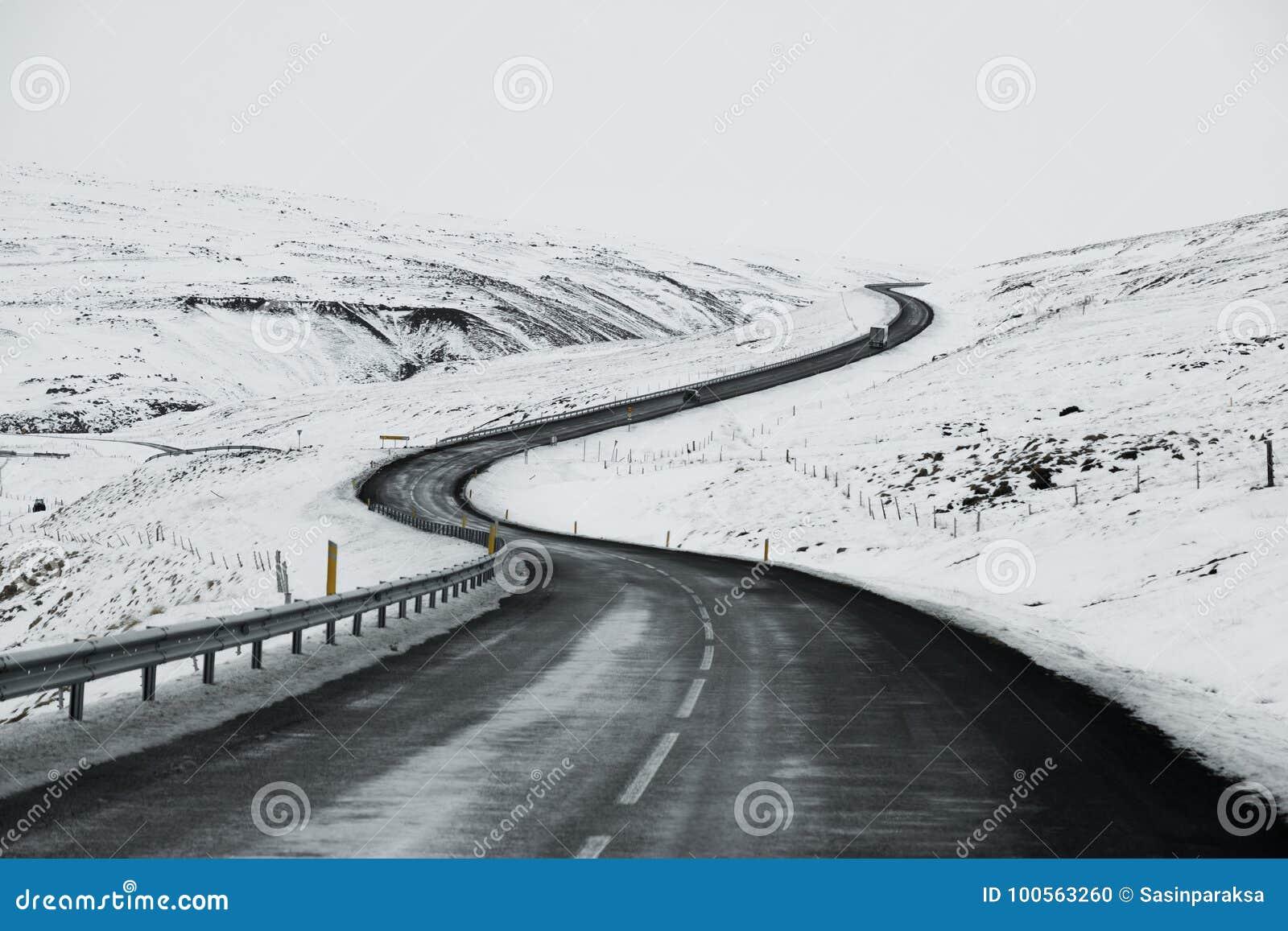 艰难路风景在冰岛的冬天 柏油路以斜向一边充分雪
