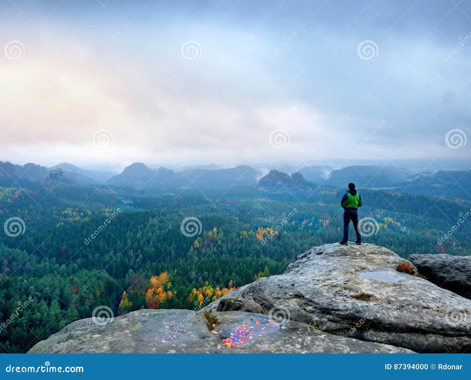 绿色防风衣的远足者,盖帽和黑暗的迁徙的长裤在山峰岩石站立