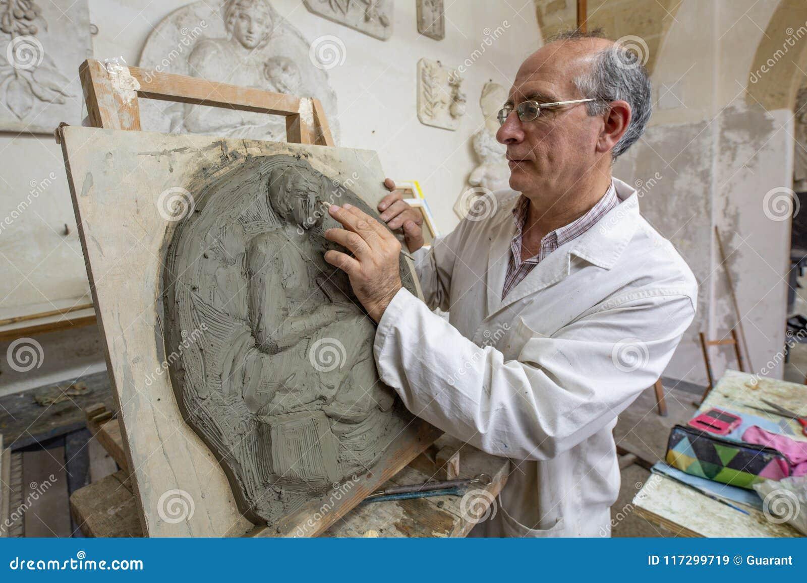 艺术家在艺术演播室在泥塑的工作
