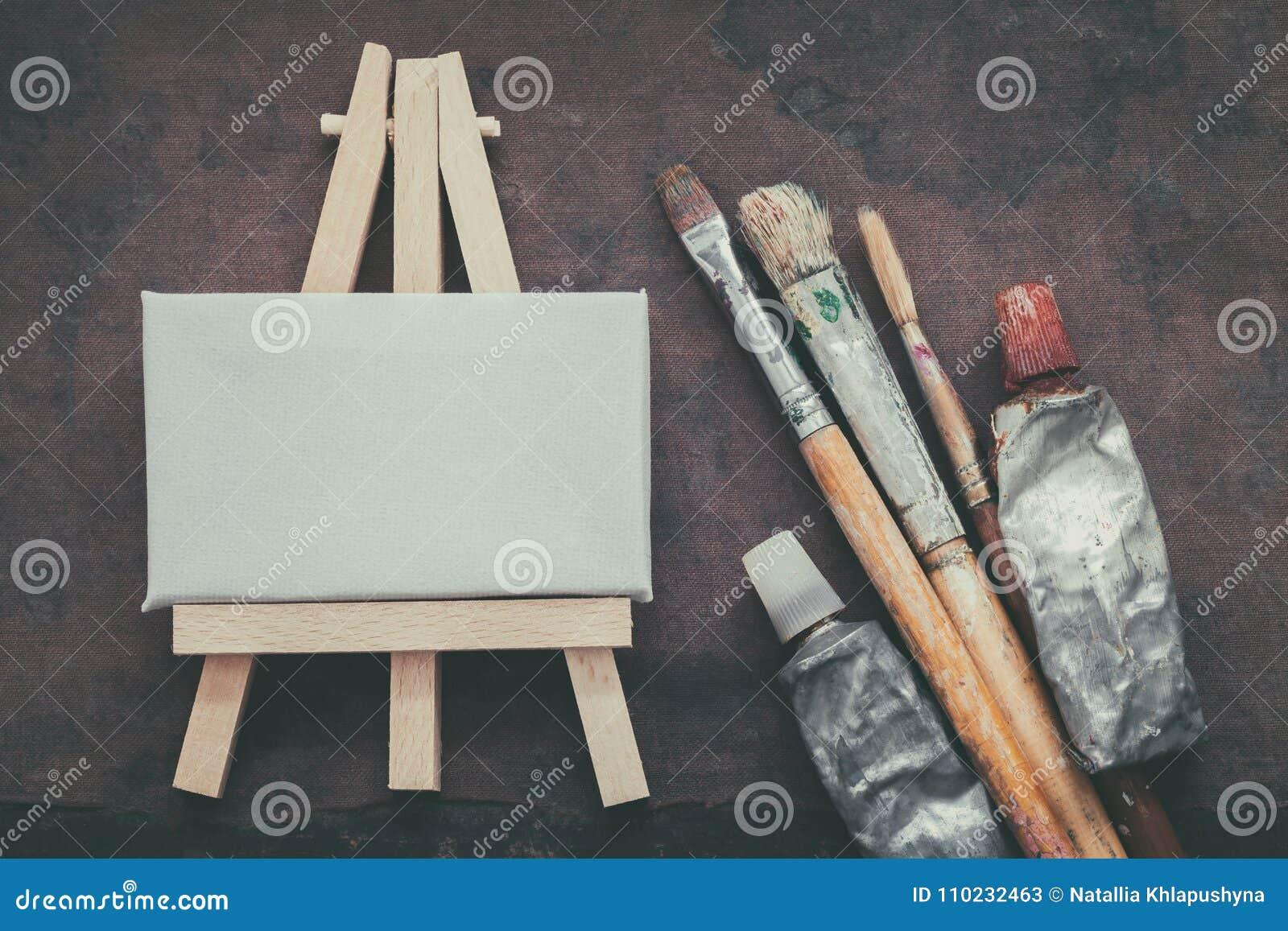 艺术家油漆刷、油漆管和小画架有帆布特写镜头的 顶视图
