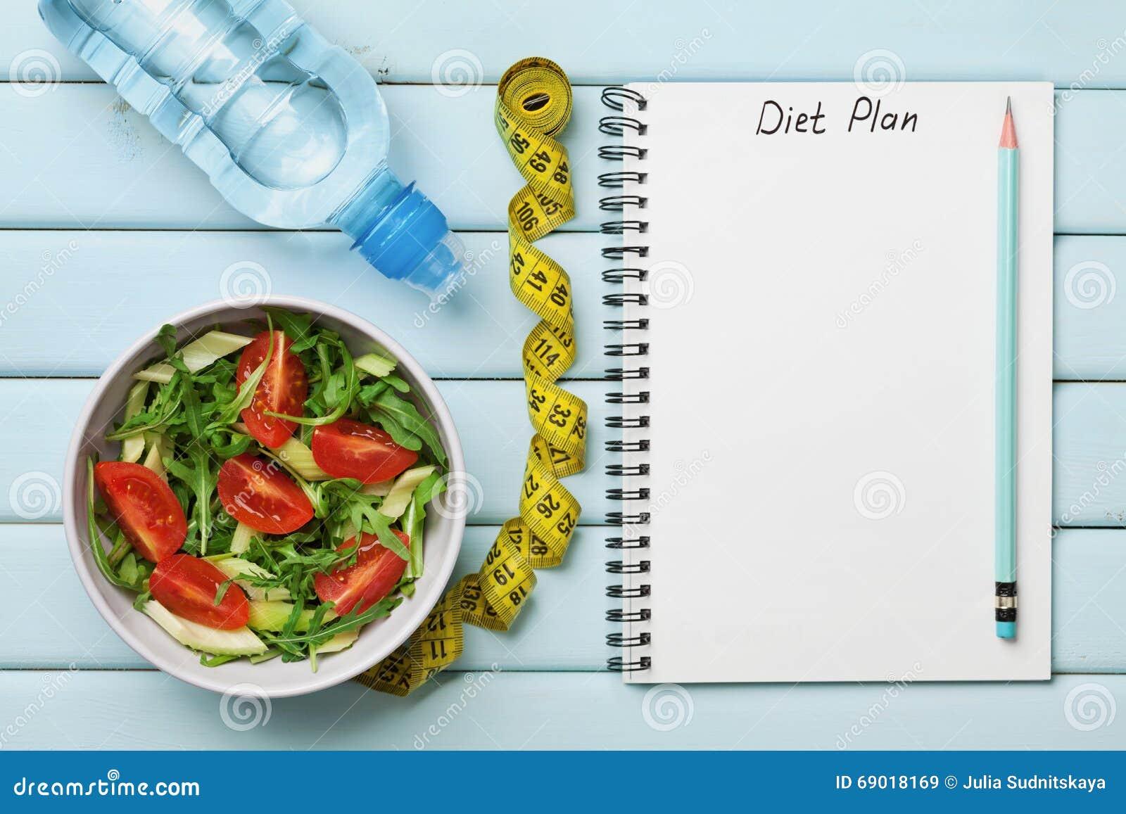 节食计划、菜单或者节目、卷尺、水和新鲜的沙拉饮食食物在蓝色背景的,减重和戒毒所概念