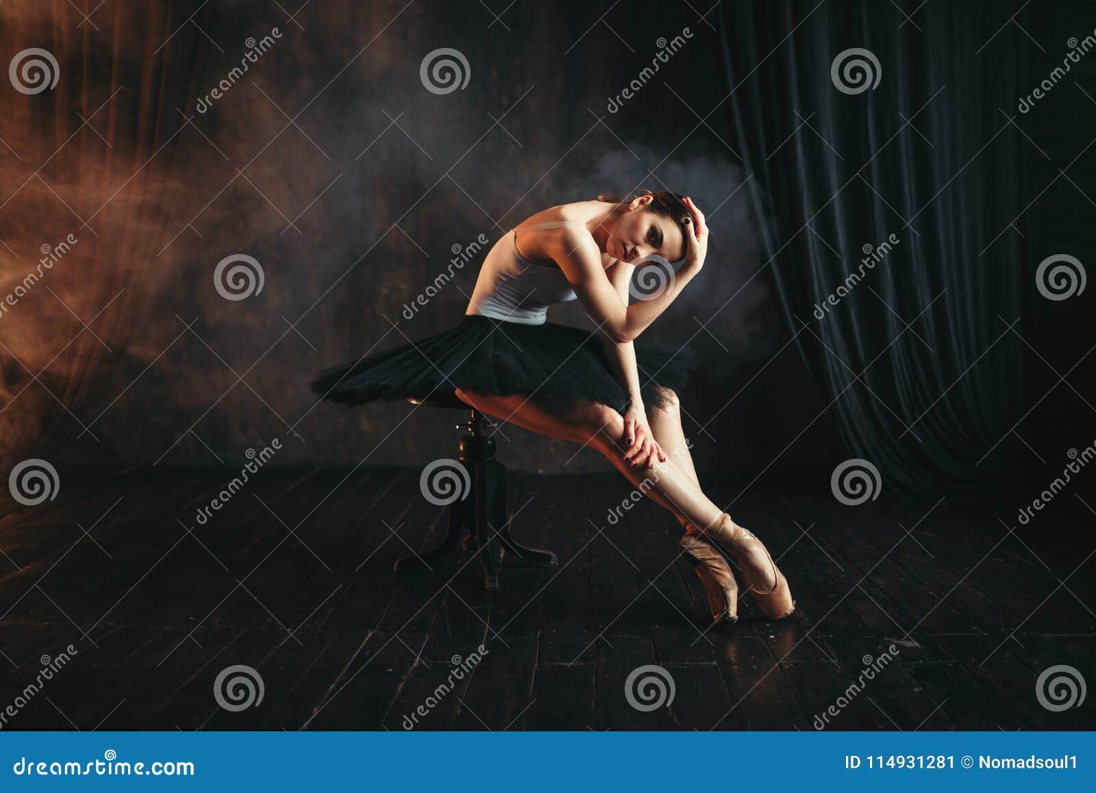 芭蕾舞女演员坐黑人行道在剧院