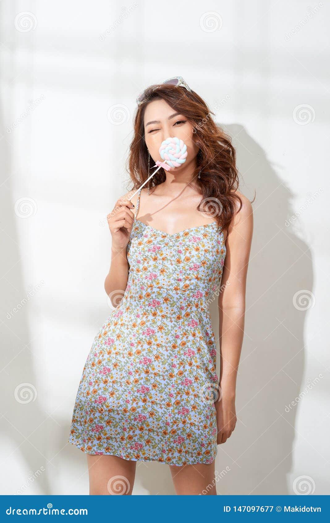 花礼服的可爱的亚裔妇女有棒棒糖的在手中