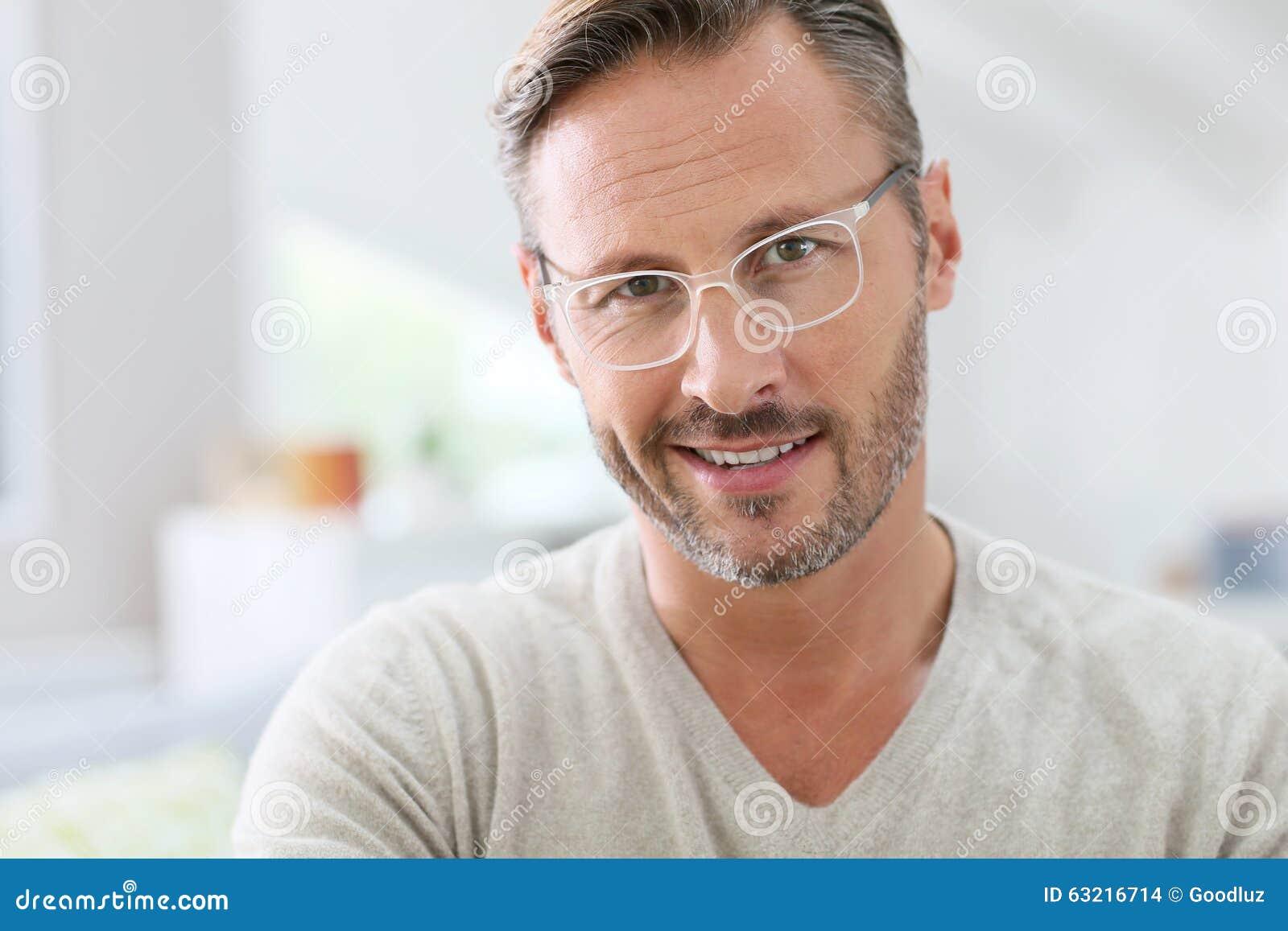英俊的中年人佩带的白色镜片