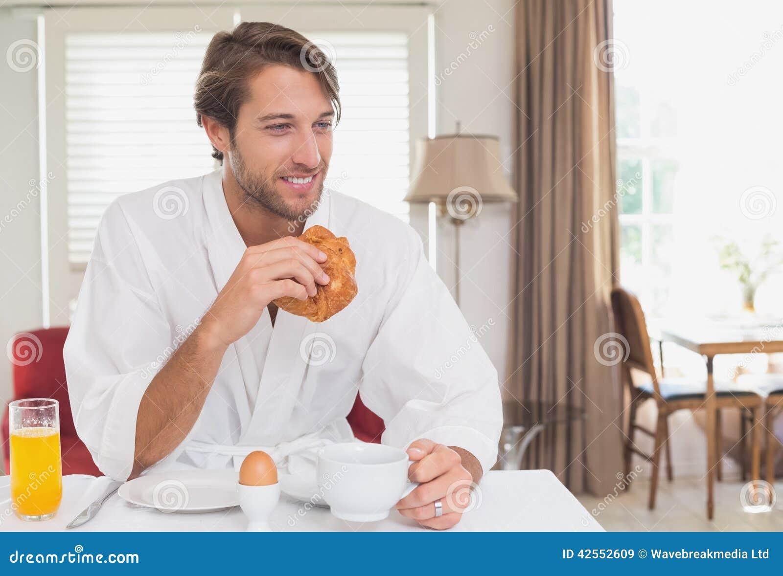 英俊的人吃早餐在他的浴巾