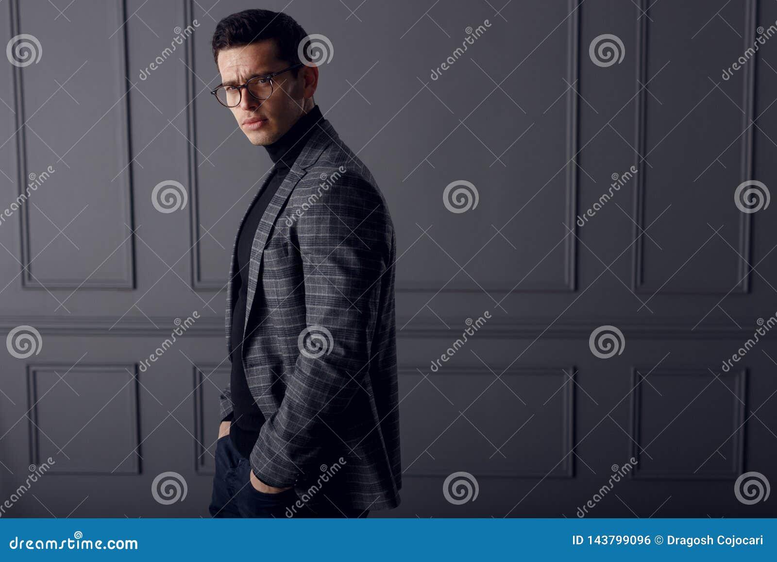 英俊的年轻深色的模型,佩带在灰色夹克,看与态度,在灰色背景 复制空间