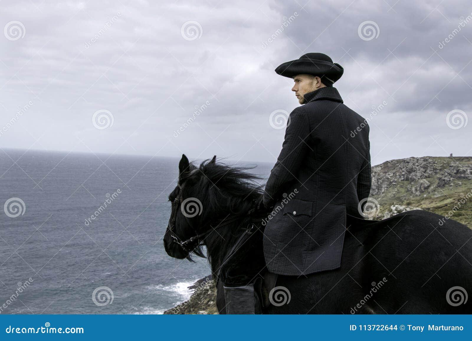 英俊的有锡矿废墟的雄性马车手摄政18世纪Poldark服装和大西洋在背景中